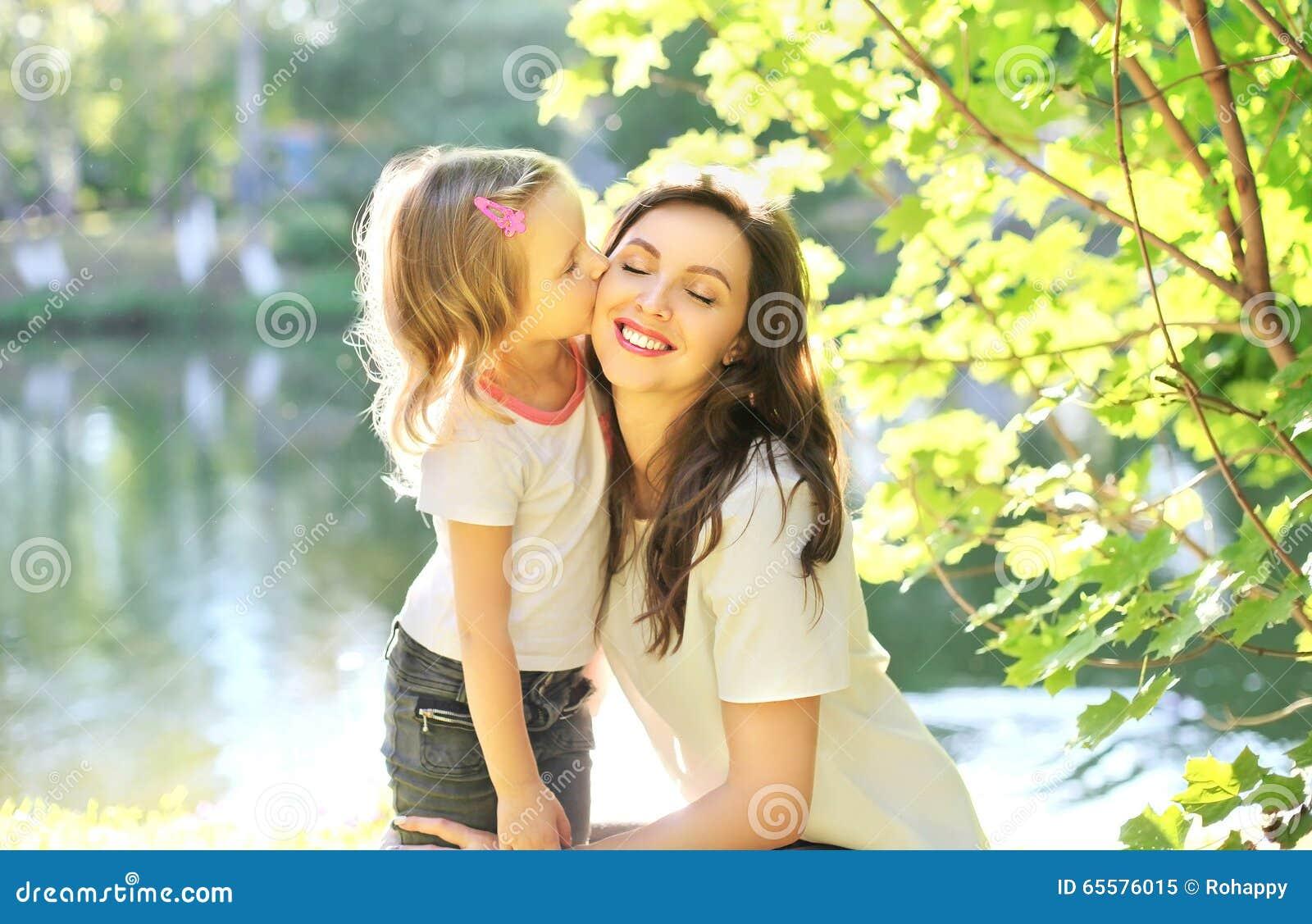 Criança da filha que beija a mãe feliz no verão