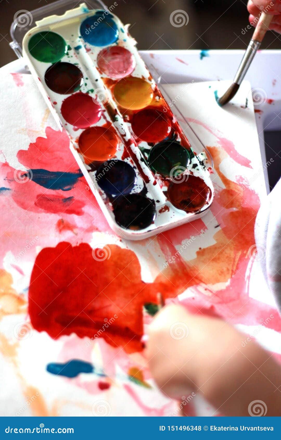 A criança da foto pinta uma escova com pinturas do mel da aquarela mãos pequenas na pintura vermelha