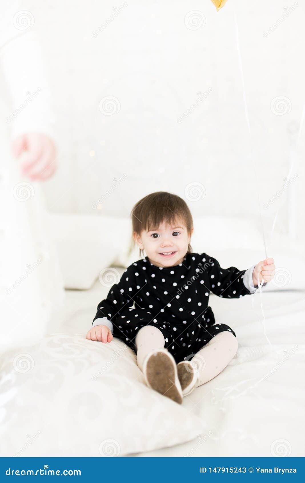 Criança de 2 anos bonito do bebê que senta-se em uma cama com um balão Festa de anos celebration