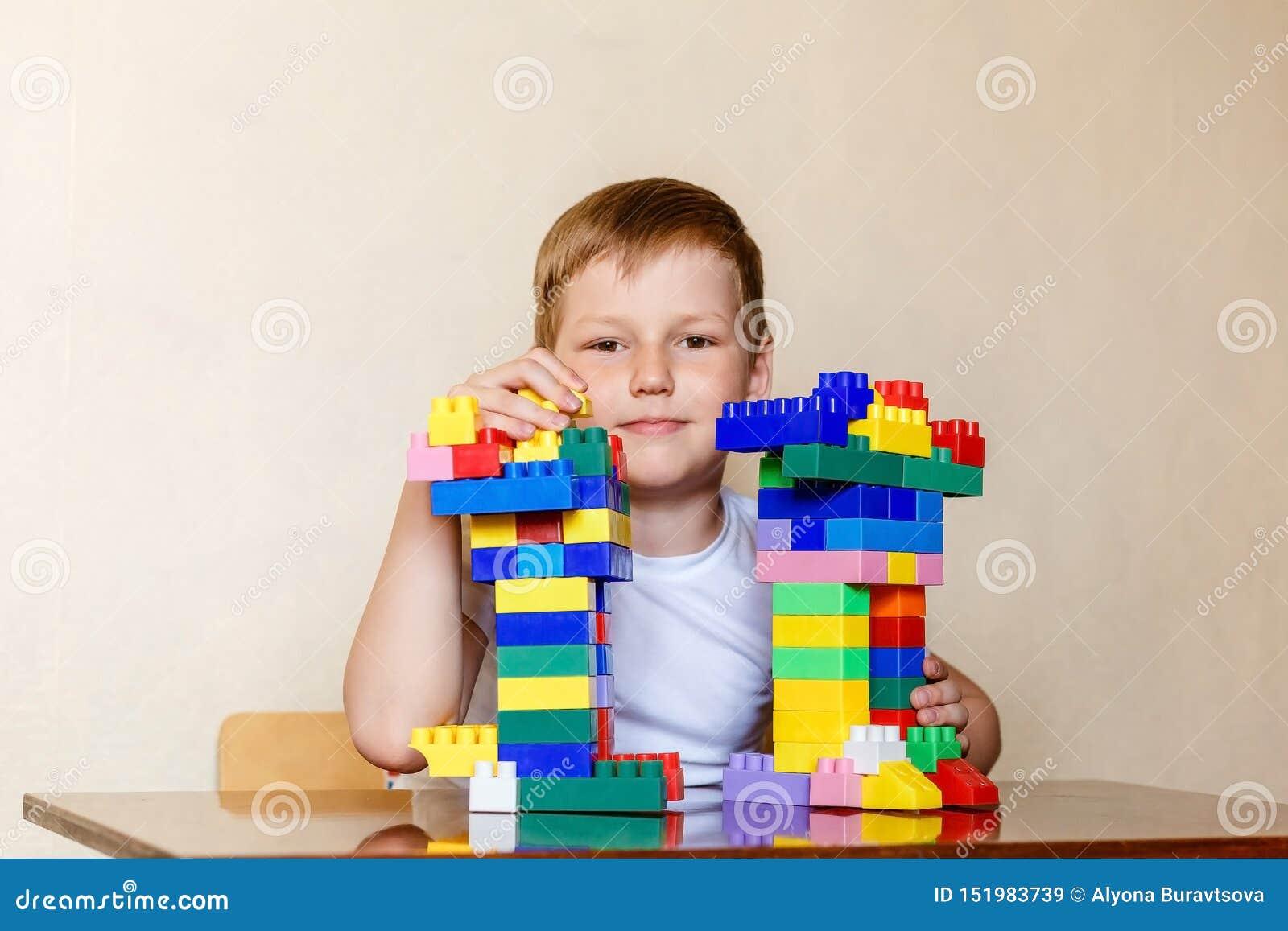 Criança de sete anos em um t-shirt branco e em um desenhista das crianças plásticas