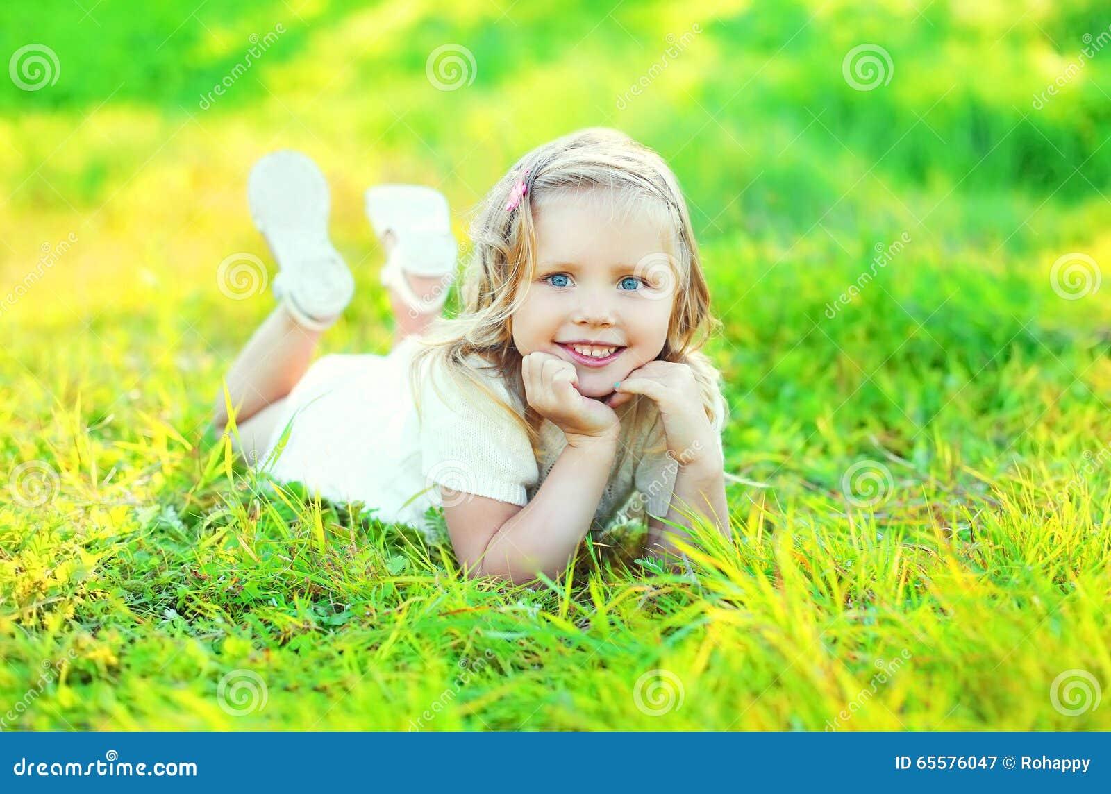 Criança de sorriso bonito feliz da menina que encontra-se na grama