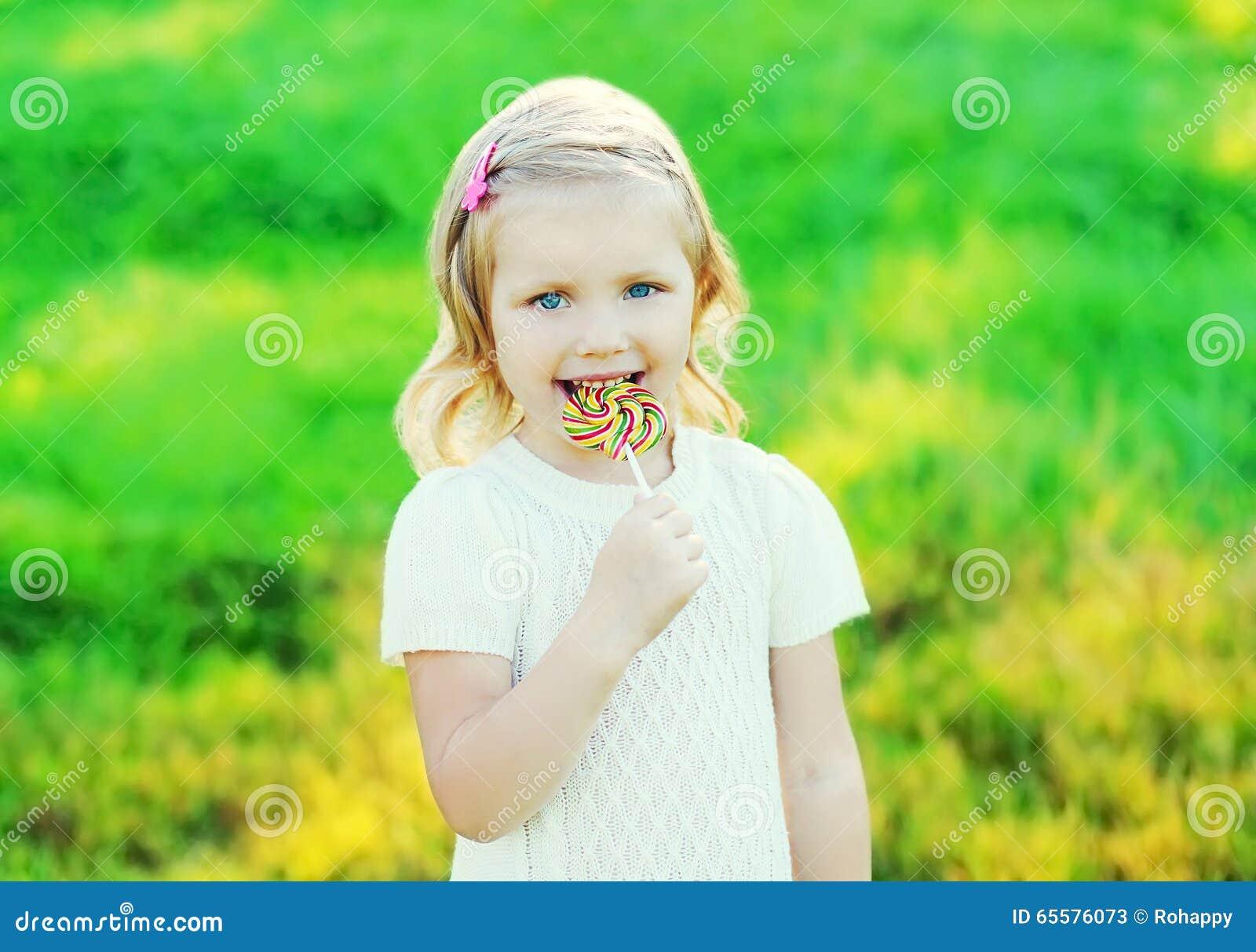 Criança de sorriso feliz com o pirulito doce do caramelo