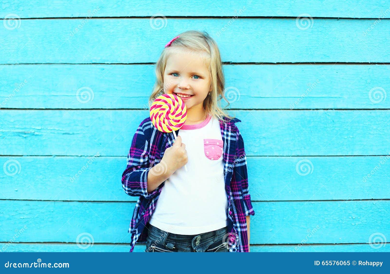 Criança de sorriso feliz com o pirulito doce do caramelo que tem o divertimento