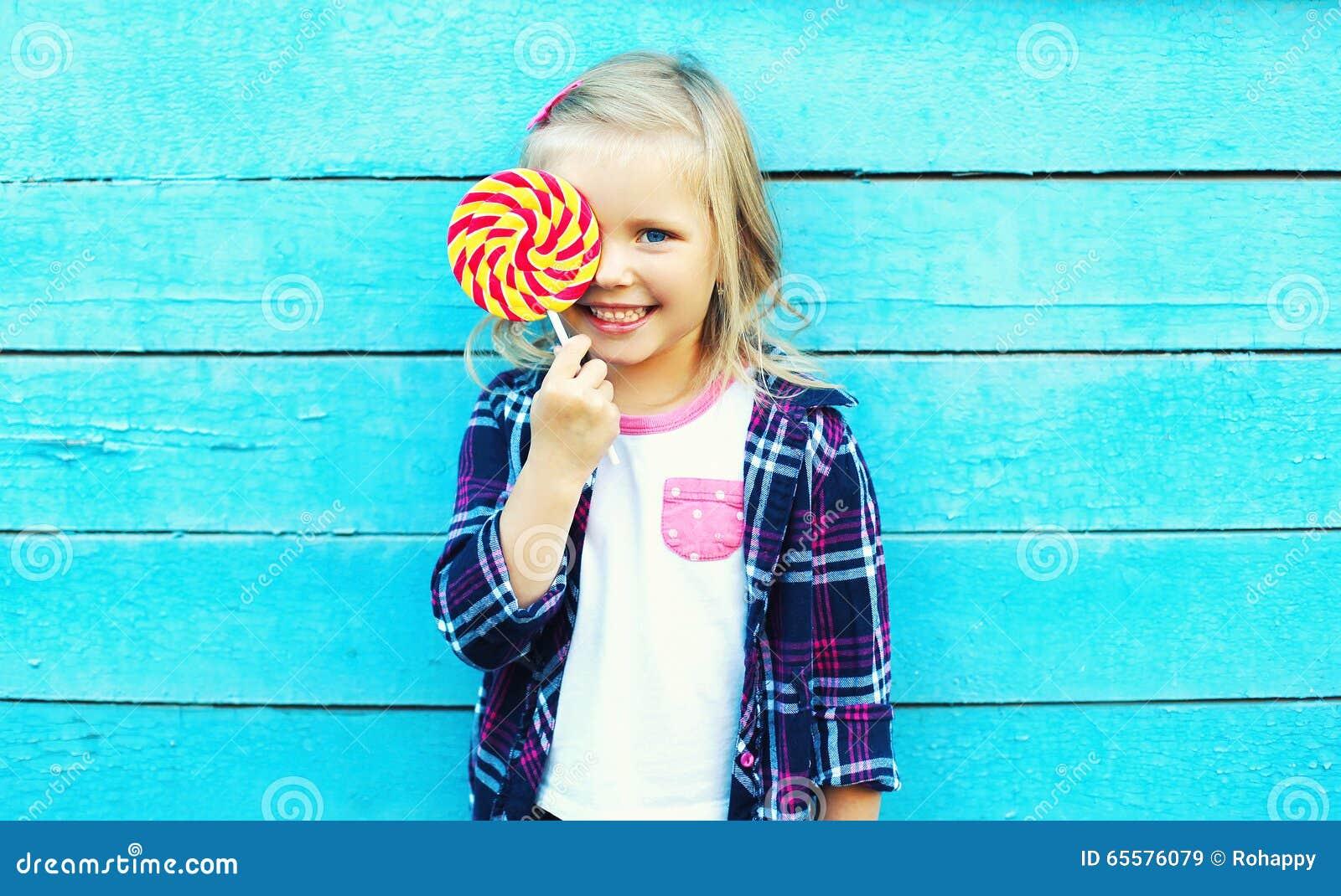 Criança de sorriso feliz com o pirulito doce que tem o divertimento