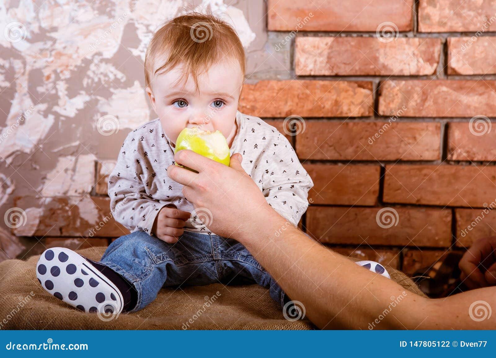 A criança de um ano senta-se em um tambor na perspectiva de uma parede de tijolo vermelho e mordeu uma maçã verde que seja mantid