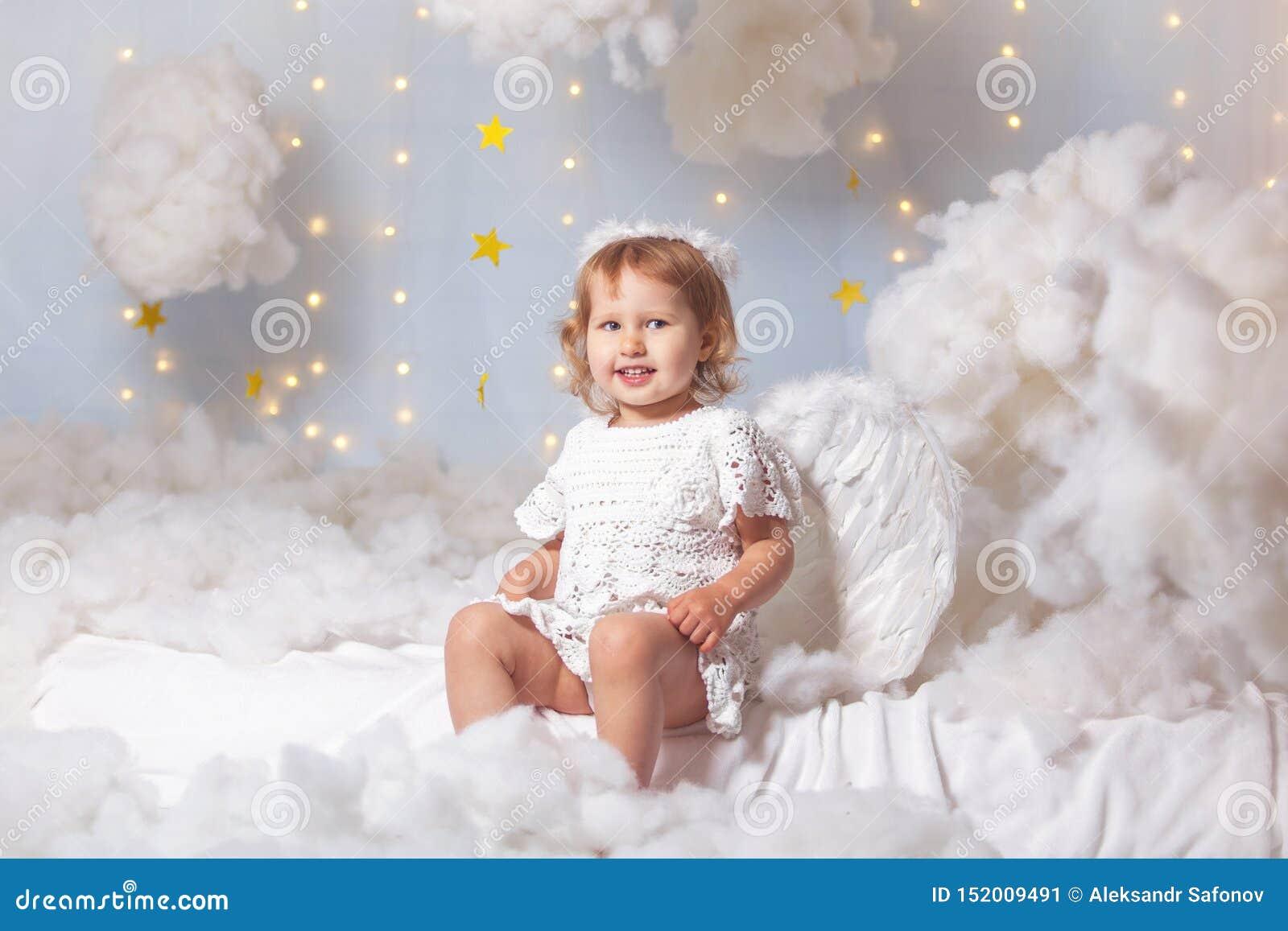 A criança do anjo está sentando os olhares das nuvens para baixo