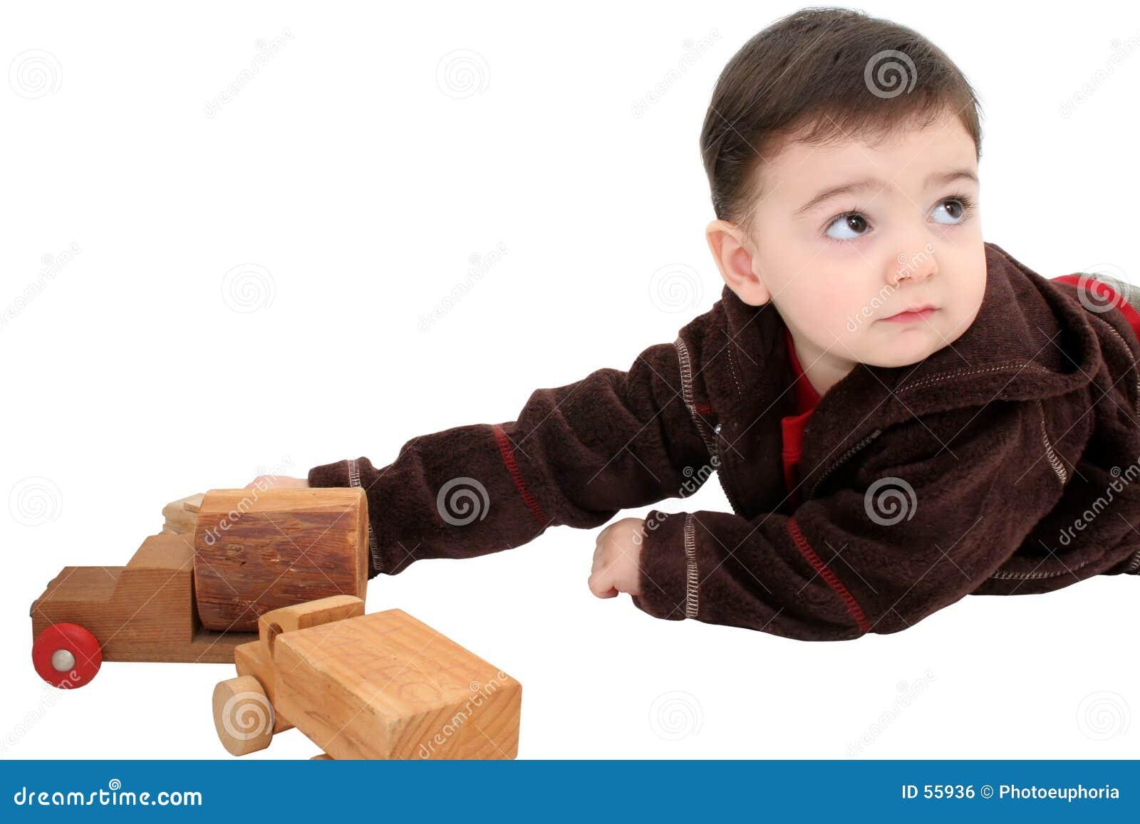 Criança do menino com os carros de madeira do brinquedo