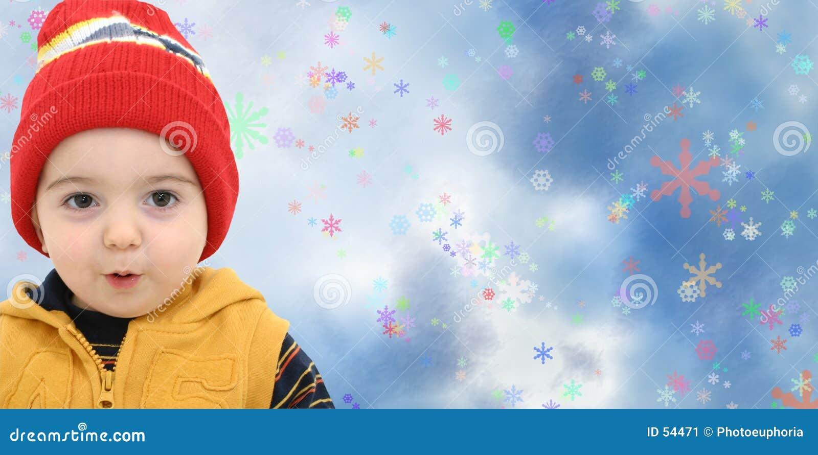 Criança do menino do inverno no fundo mágico do floco de neve