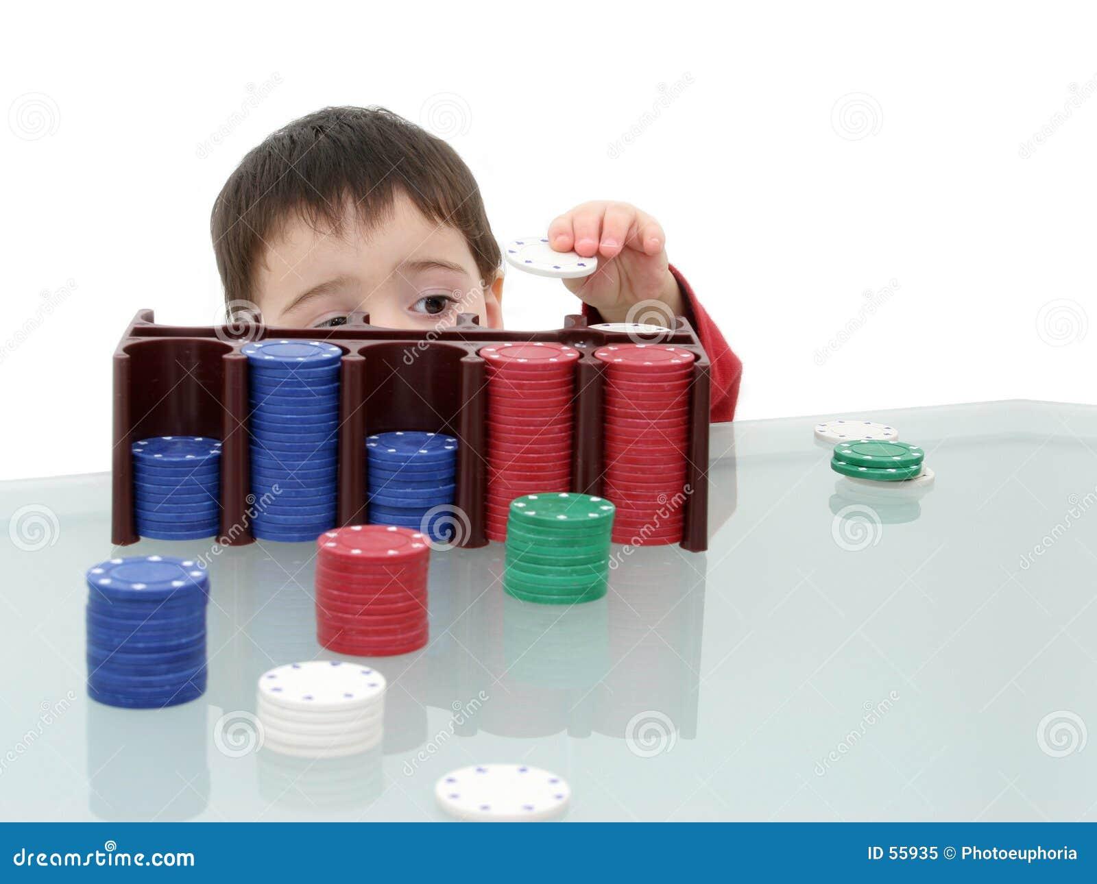 Criança do menino que joga com microplaquetas do póquer