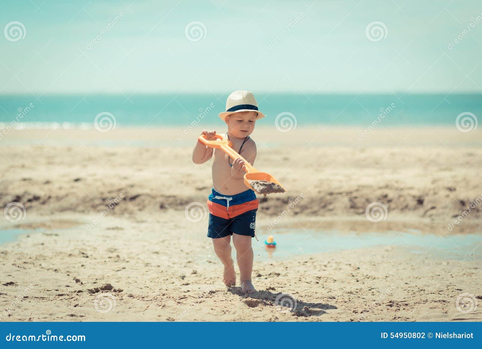 Criança do rapaz pequeno que anda na praia