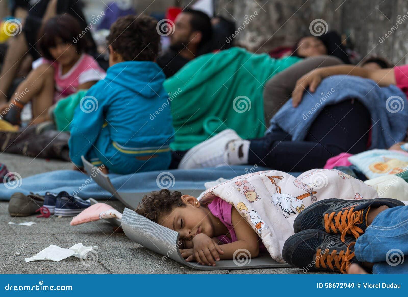 Criança do refugiado que dorme no estação de caminhos-de-ferro de Keleti em Budapest