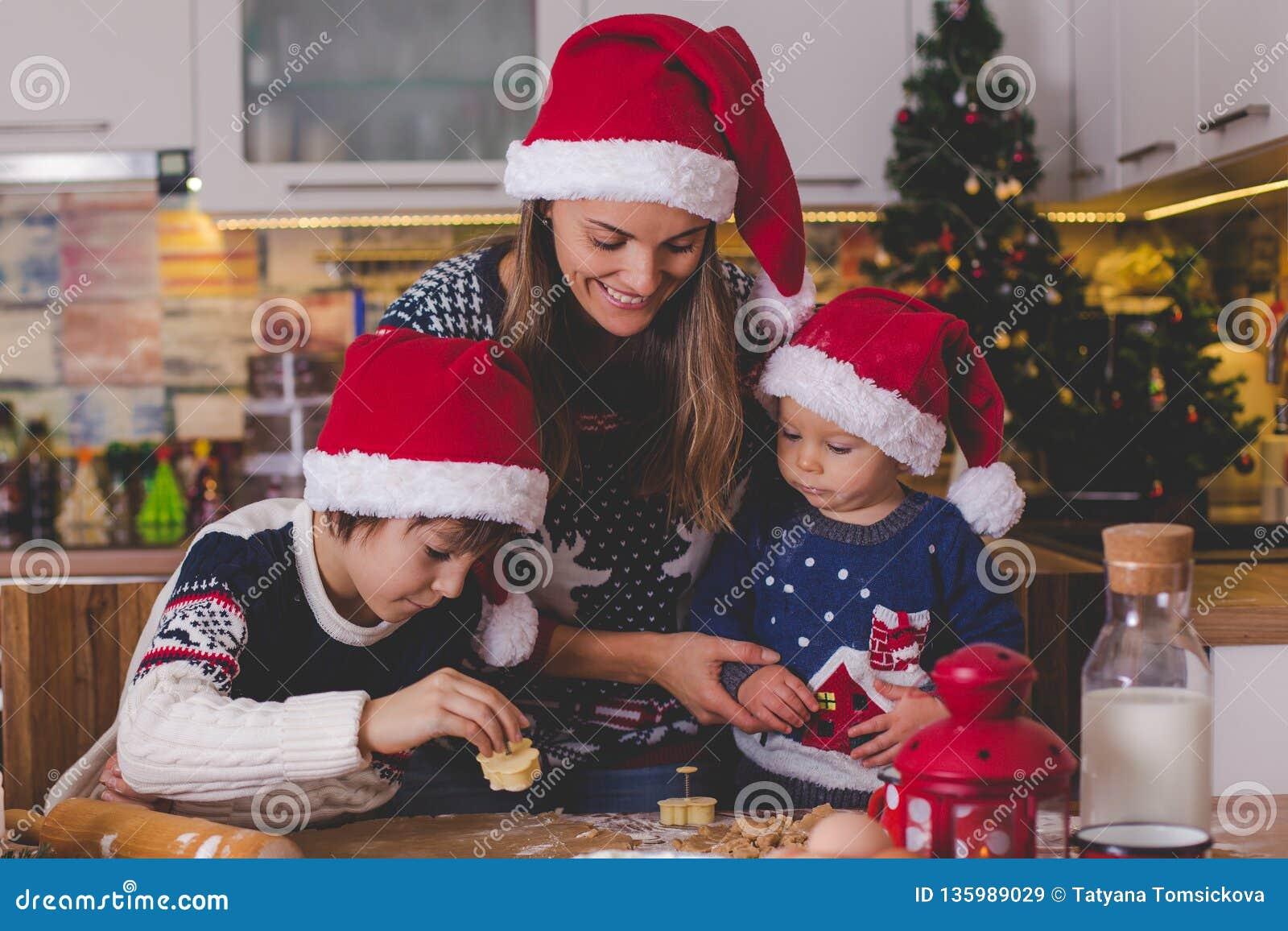 Criança doce da criança e seu irmão mais idoso, meninos, mamã de ajuda que prepara cookies do Natal em casa