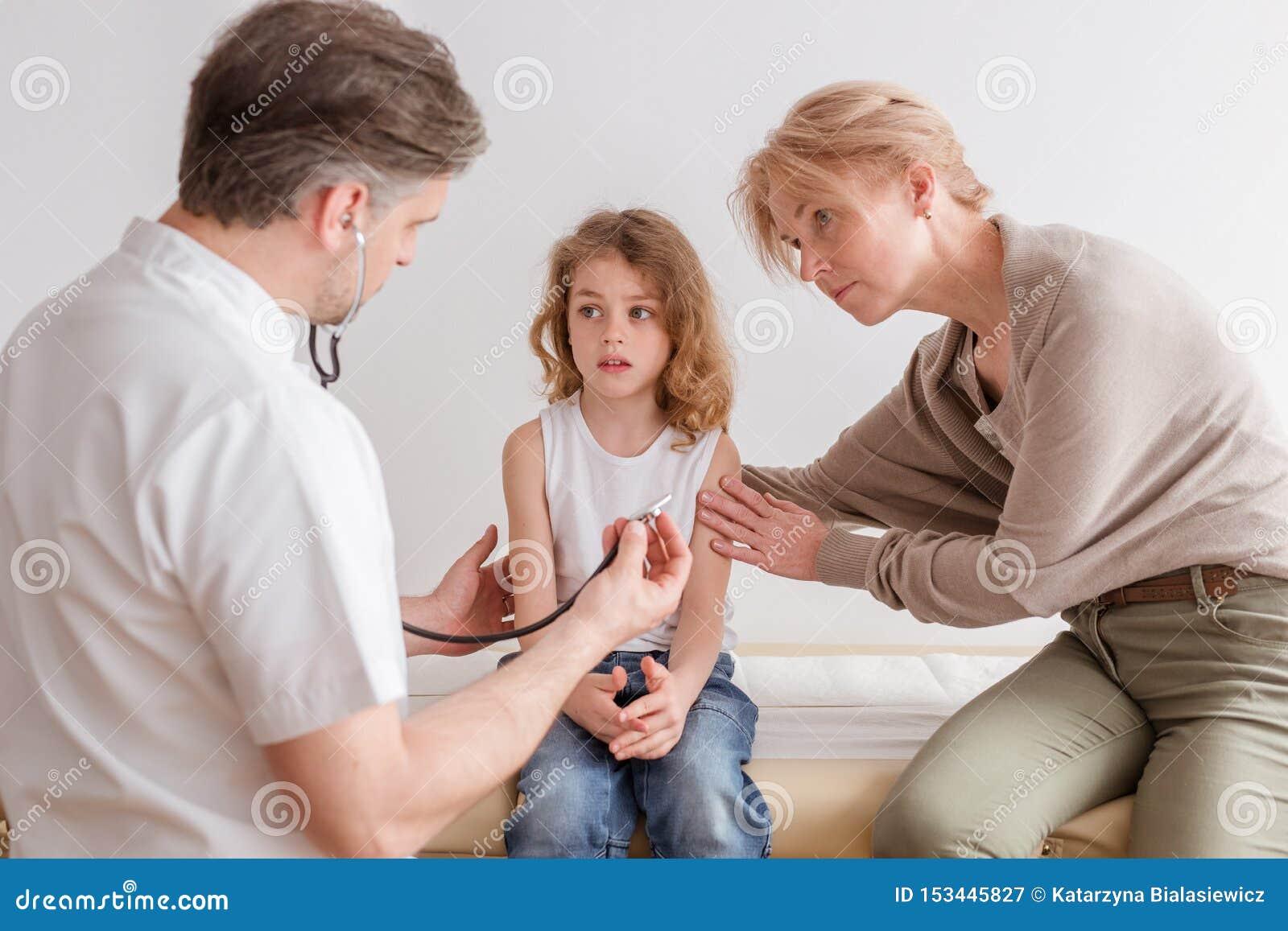 Criança doente com sintomas da pneumonia e doutor profissional no hospital