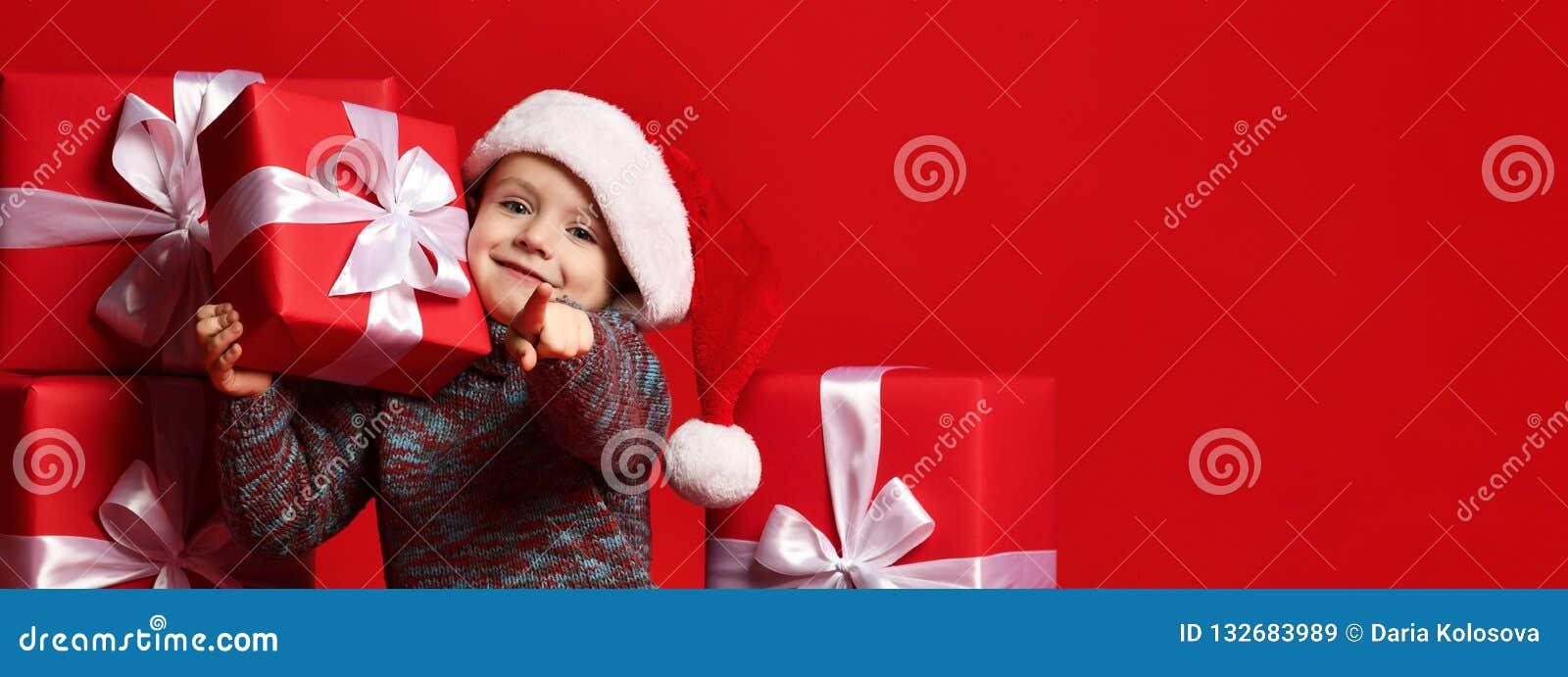 Criança engraçada de sorriso no chapéu vermelho de Santa que mantém o presente do Natal disponivel Conceito do Natal