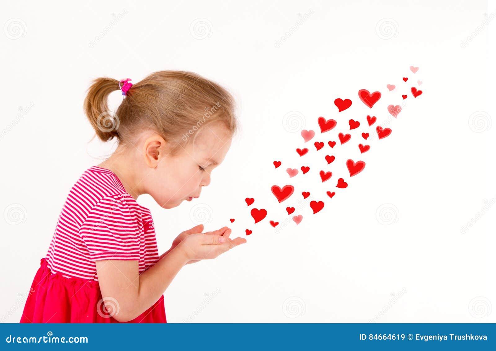 A criança está enviando beijos dados forma coração