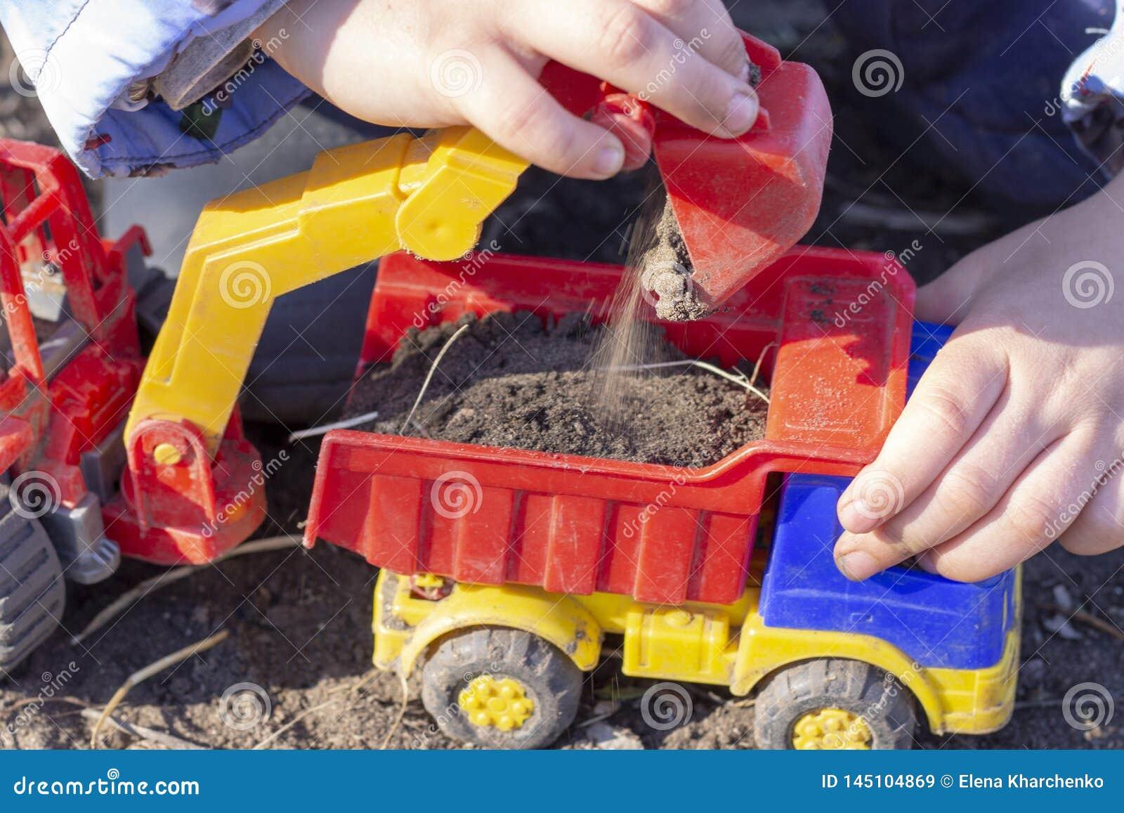 A criança está jogando na rua com areia; carrega a terra em um brinquedo do caminhão basculante