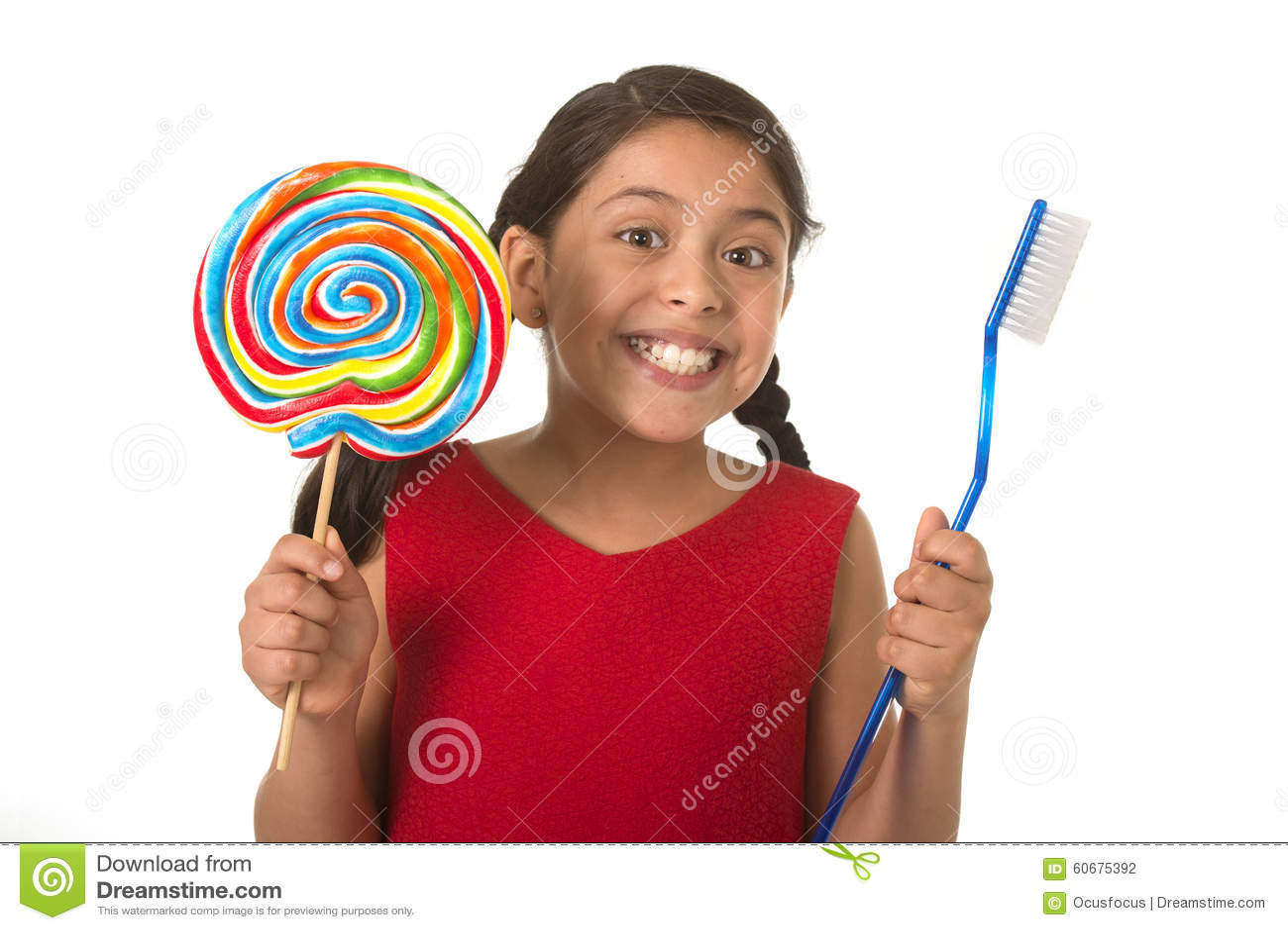 Criança fêmea bonito que guarda doces espirais grandes do pirulito e a escova de dentes enorme no conceito dos cuidados dentários