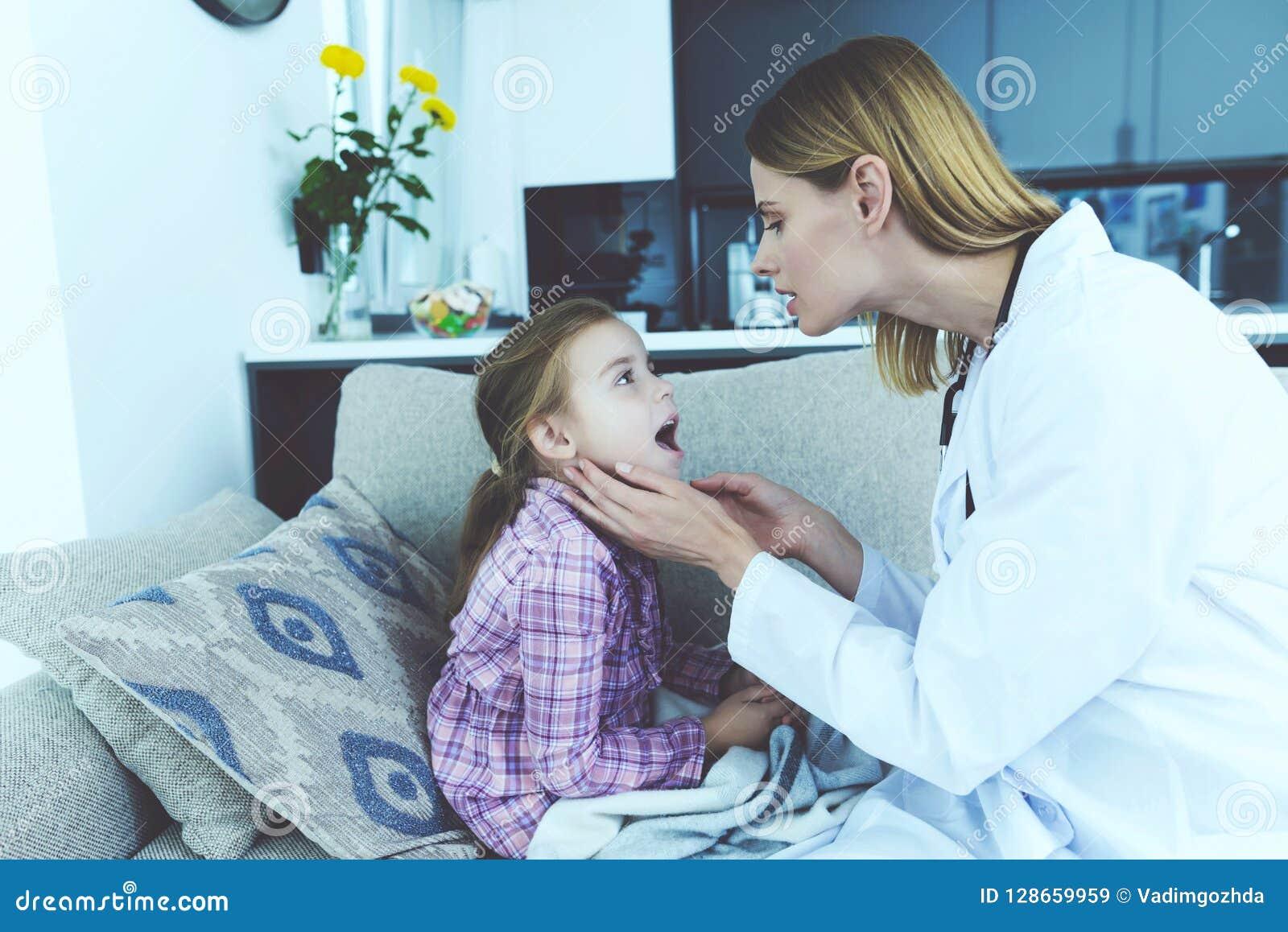 Criança fêmea do doutor Examines Pretty Sick em casa