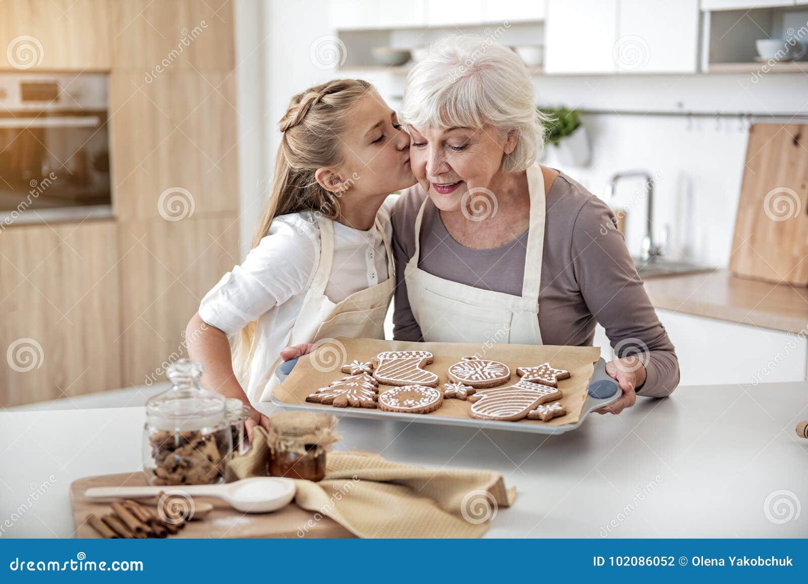 Criança feliz que agradece à avó para a pastelaria doce