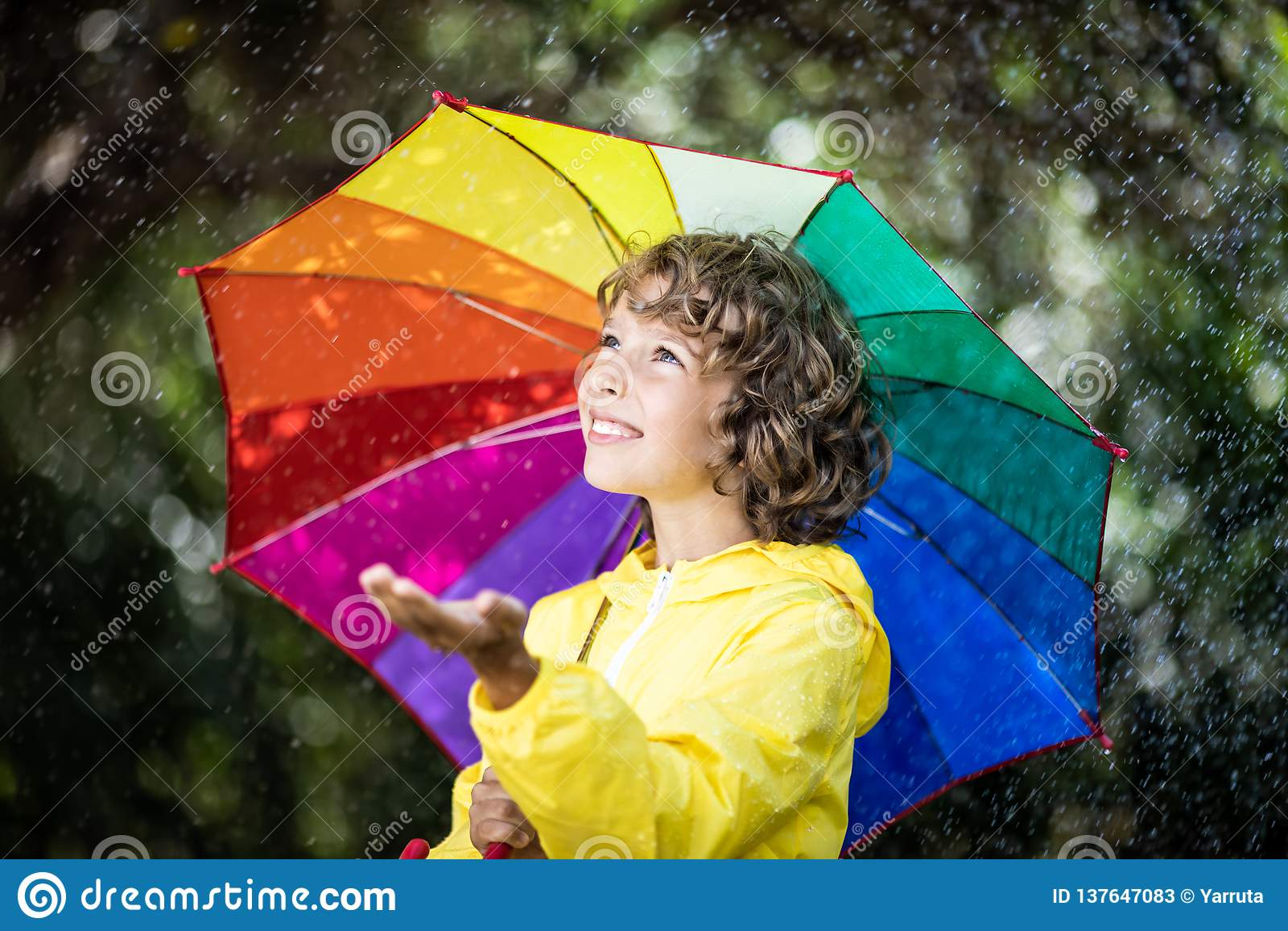 Criança feliz que joga na chuva