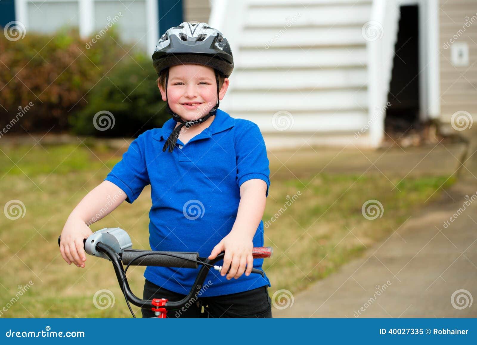 Criança feliz que monta sua bicicleta