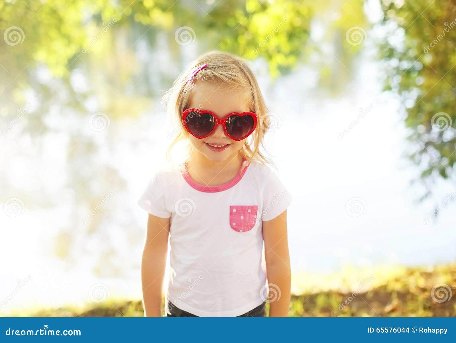Criança feliz vestindo os óculos de sol que têm o divertimento no verão