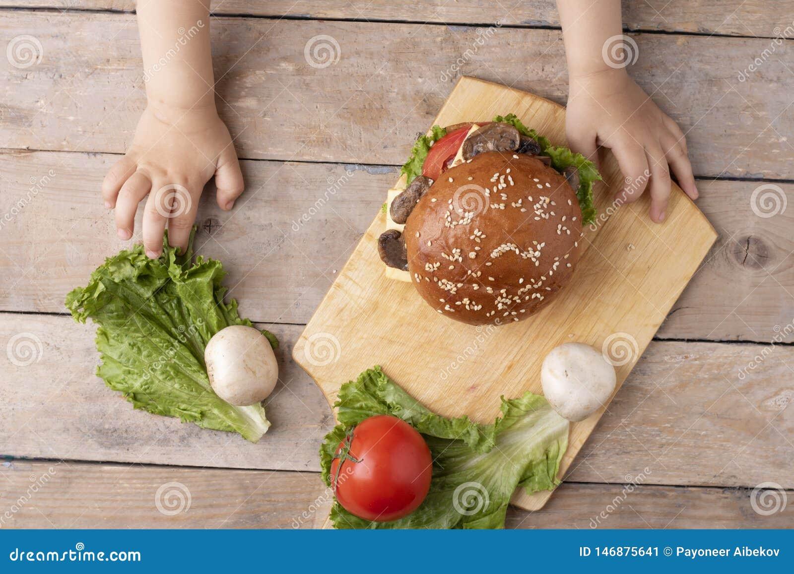 A criança guarda o hamburguer do cogumelo acima da placa de desbastamento na tabela de madeira