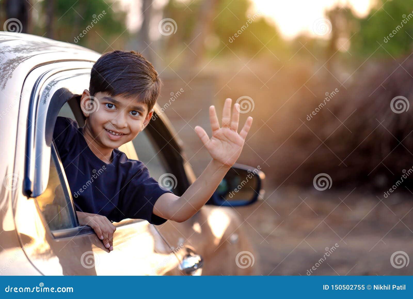 Criança indiana bonito que acena da janela de carro