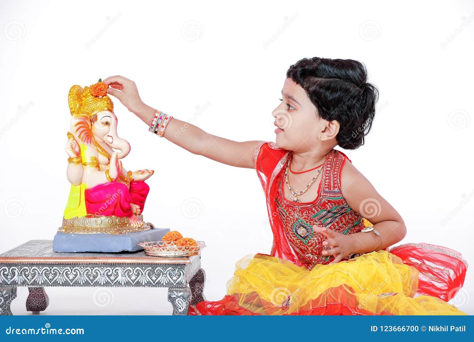 Criança indiana pequena da menina com ganesha e rezar do senhor, festival indiano do ganesh