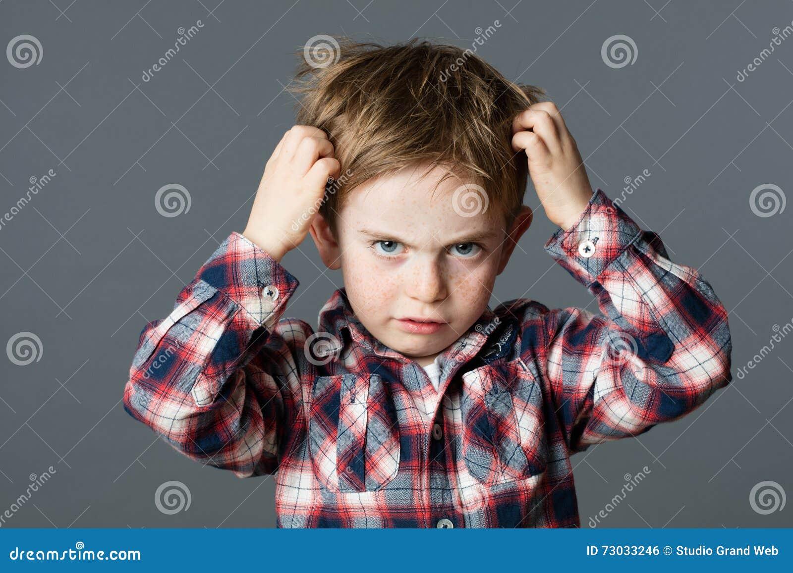 Criança infeliz que risca seu cabelo para os piolhos principais ou as alergias
