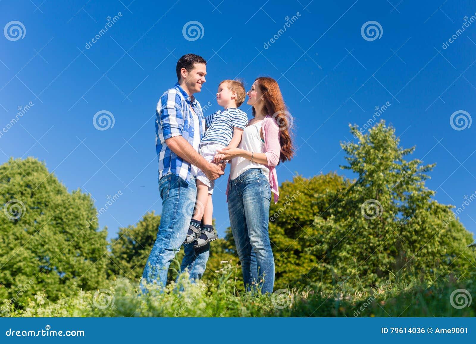 Criança levando da família, pais que estão no prado