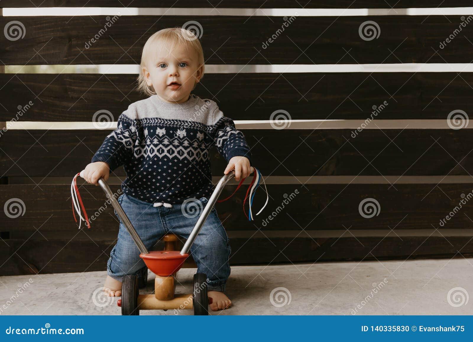 A criança loura pequena bonito adorável preciosa do menino da criança do bebê que joga fora em Toy Bicycle Scooter Mobile Smiling