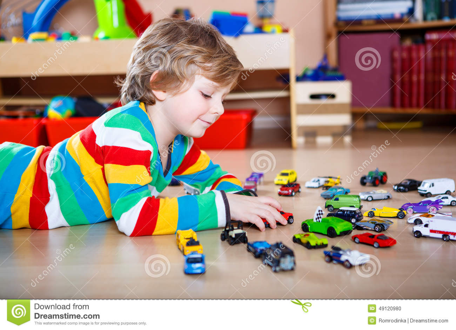 Criança loura pequena engraçada feliz que joga com lotes de carros do brinquedo