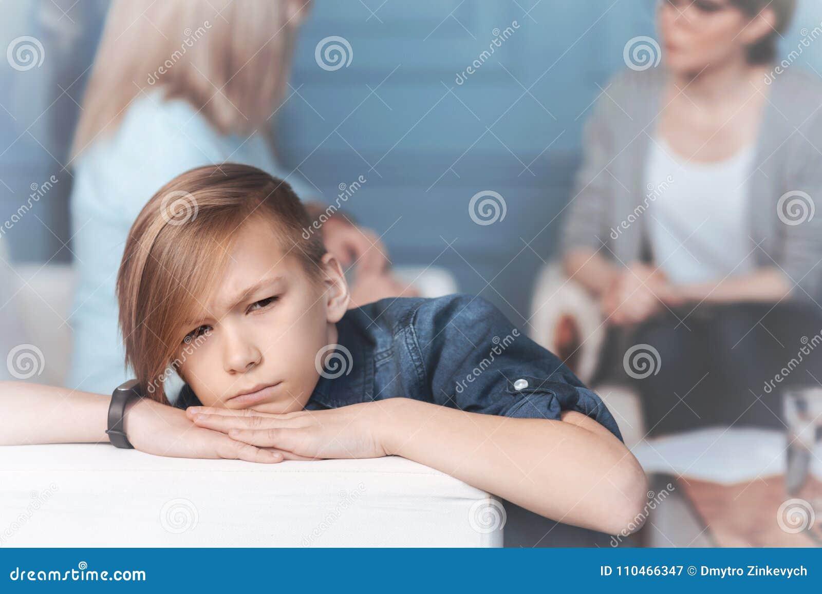 Criança mal-humorada que relaxa no sofá no escritório do psicólogo
