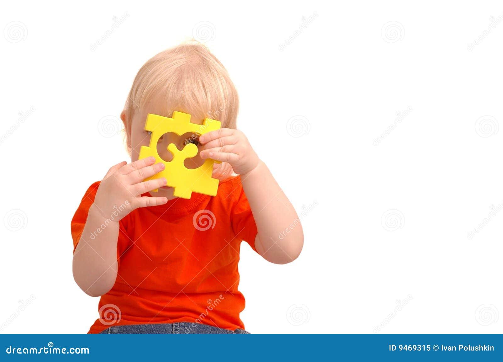 A criança mantem o enigma com numeral e