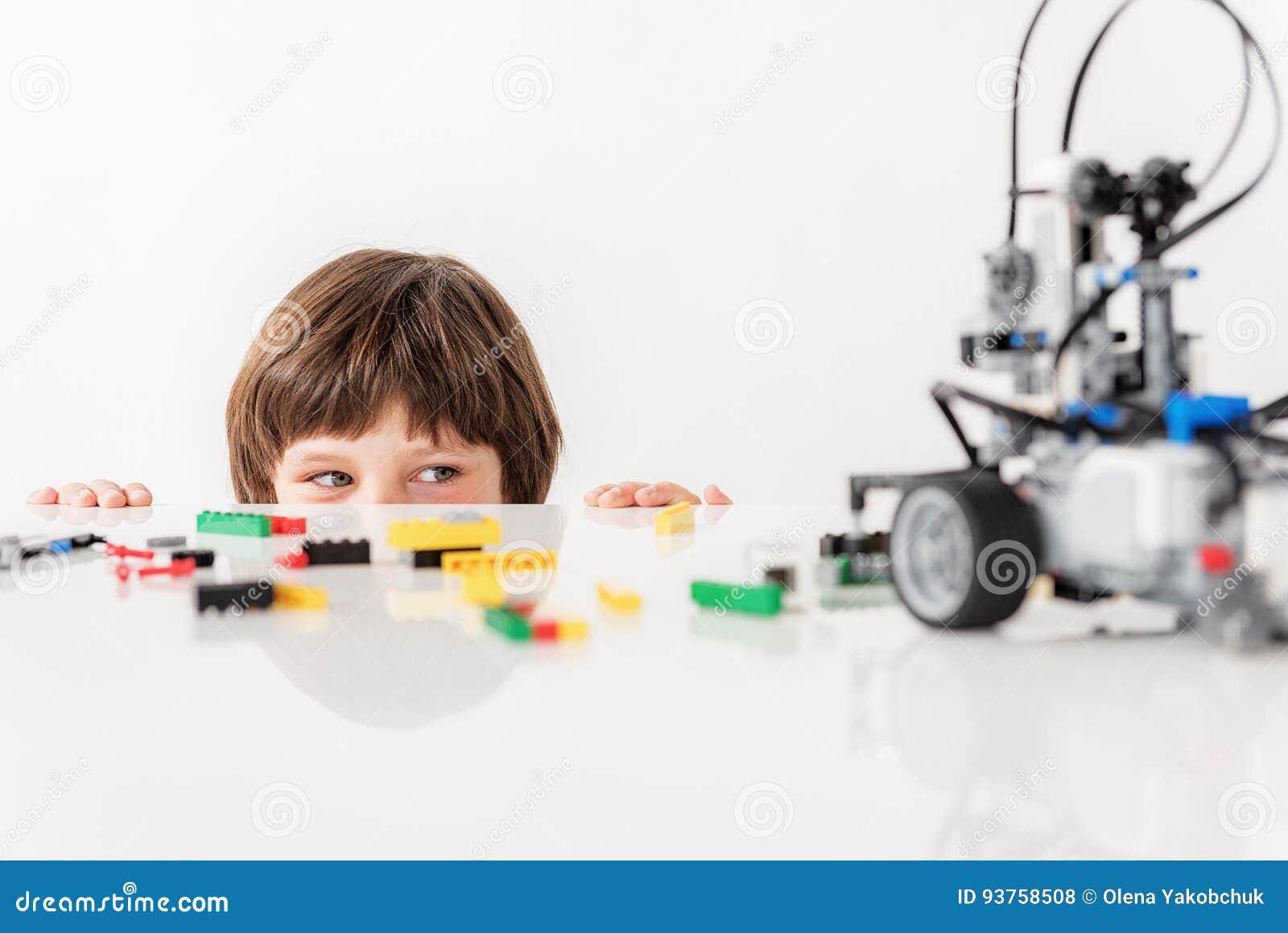 Criança masculina manhoso interessada que olha para o brinquedo