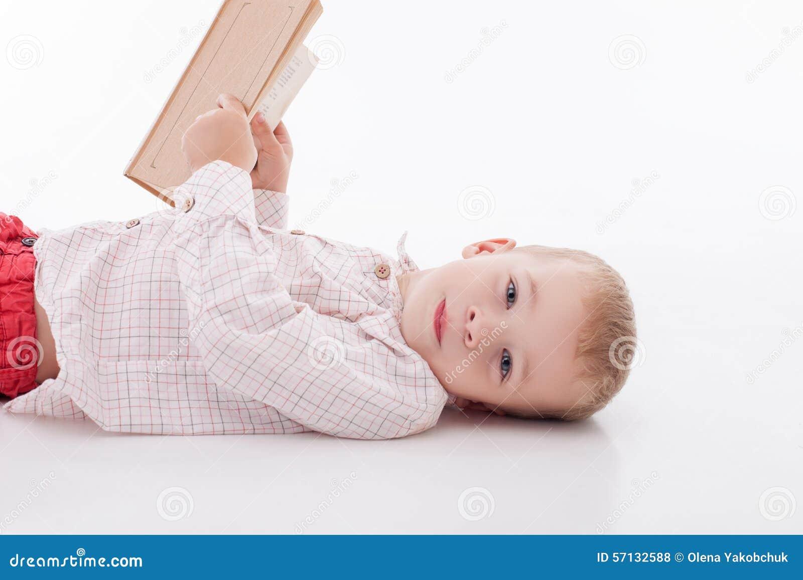 A criança masculina pequena alegre está aprendendo letras
