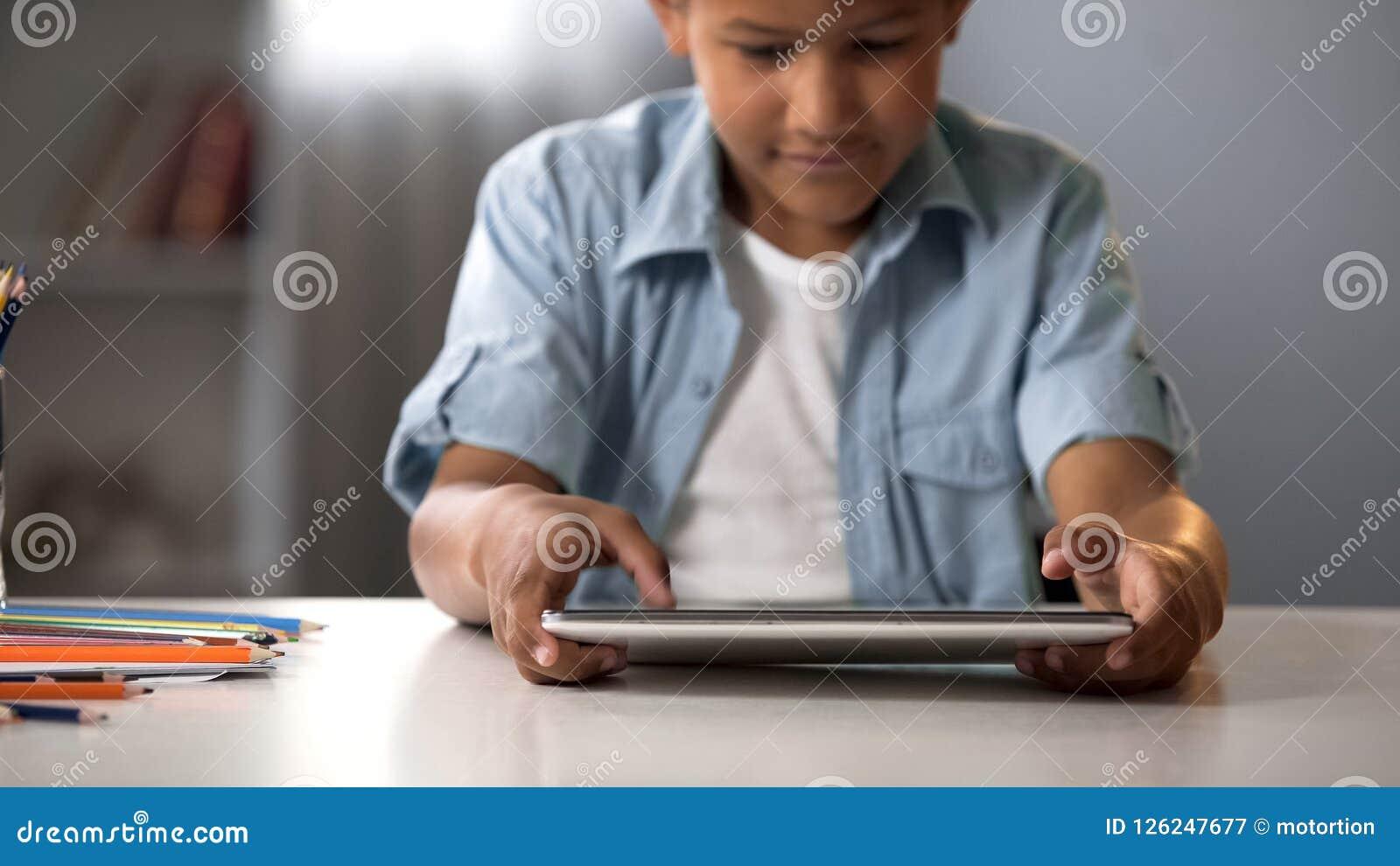 Criança masculina que joga entusiasticamente na tabuleta, apego do jogo, problema do comportamento