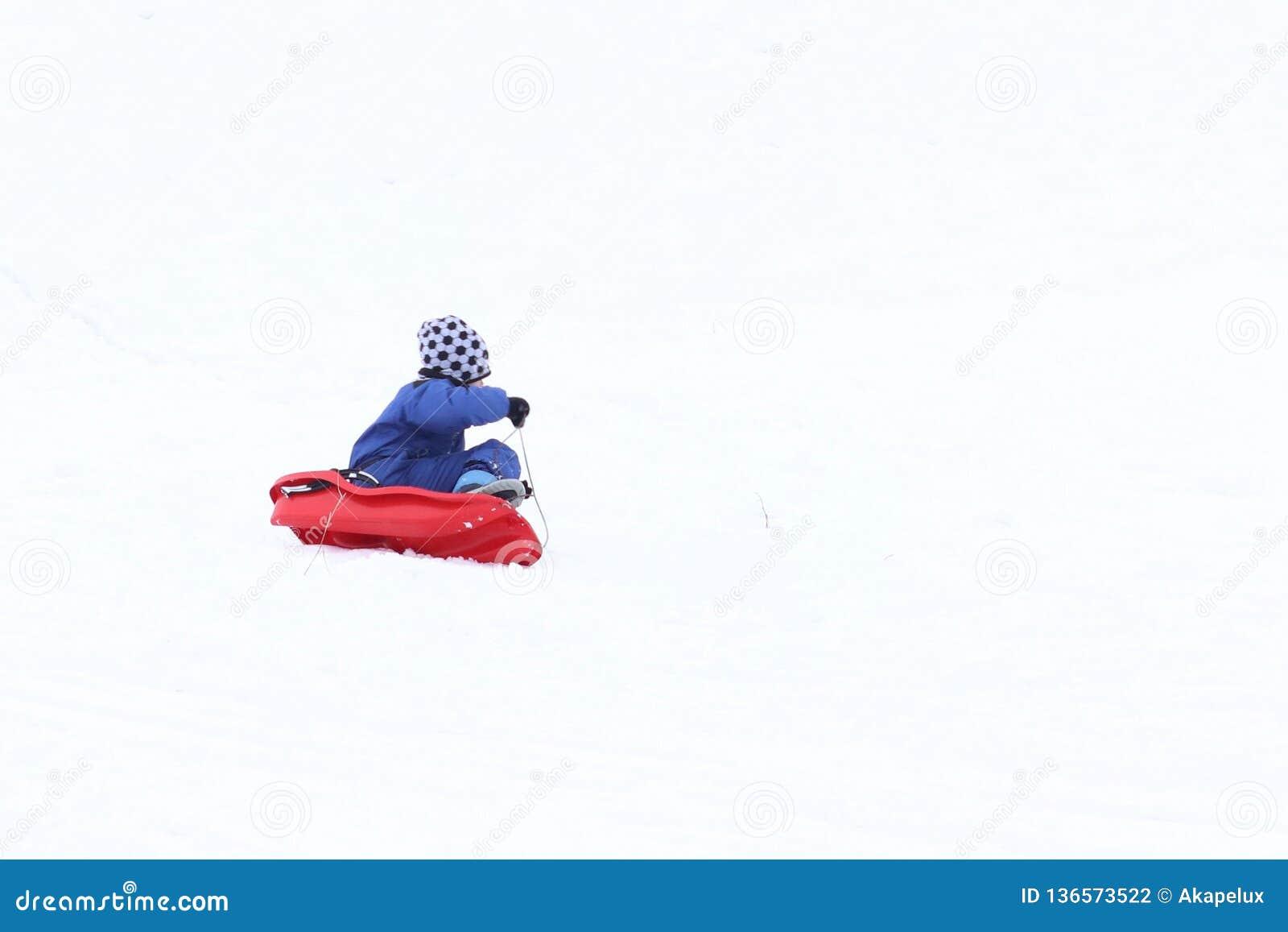 A criança monta no inverno em um trenó em uma rua nevado Atividade de crescer acima a geração no ar fresco Saudável