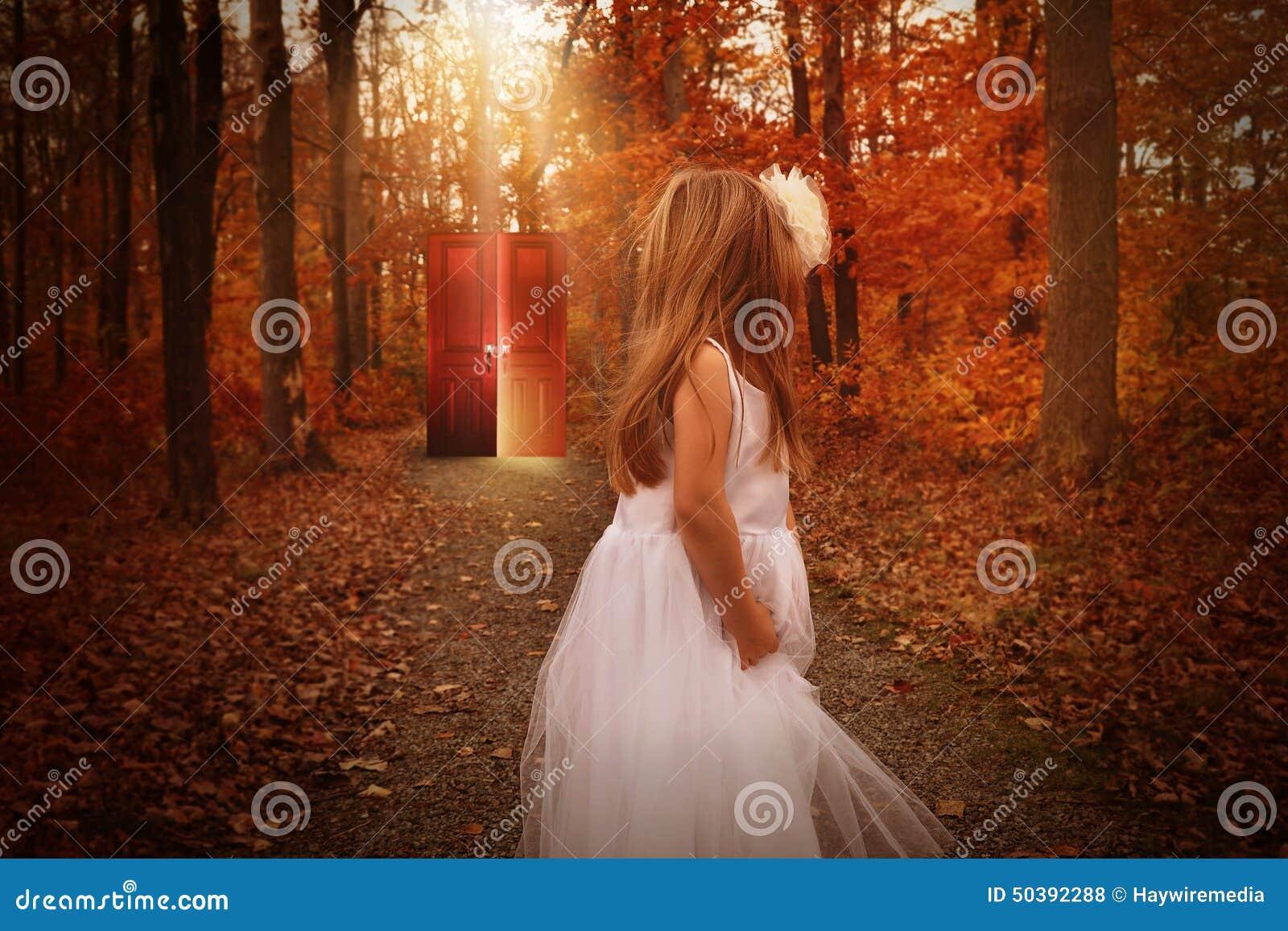 Criança nas madeiras que olham a porta vermelha de incandescência