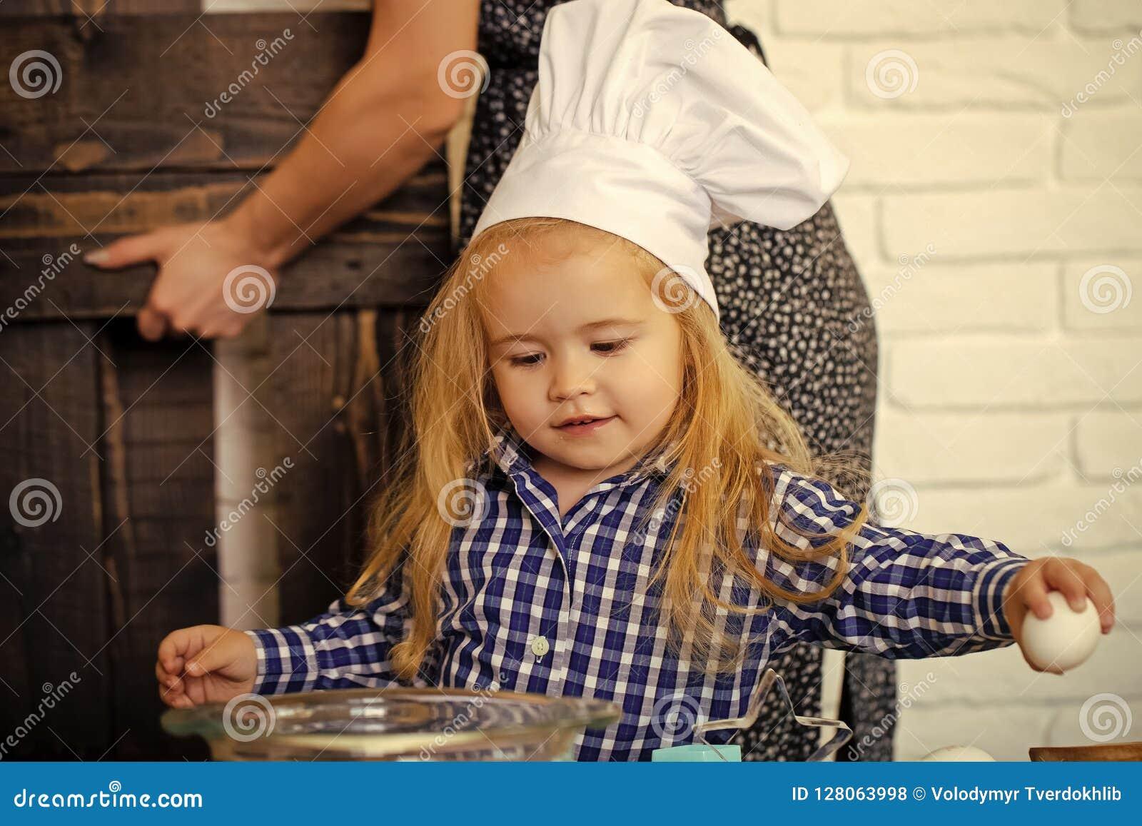 Criança no chapéu do cozinheiro chefe que quebra o ovo da bacia na cozinha