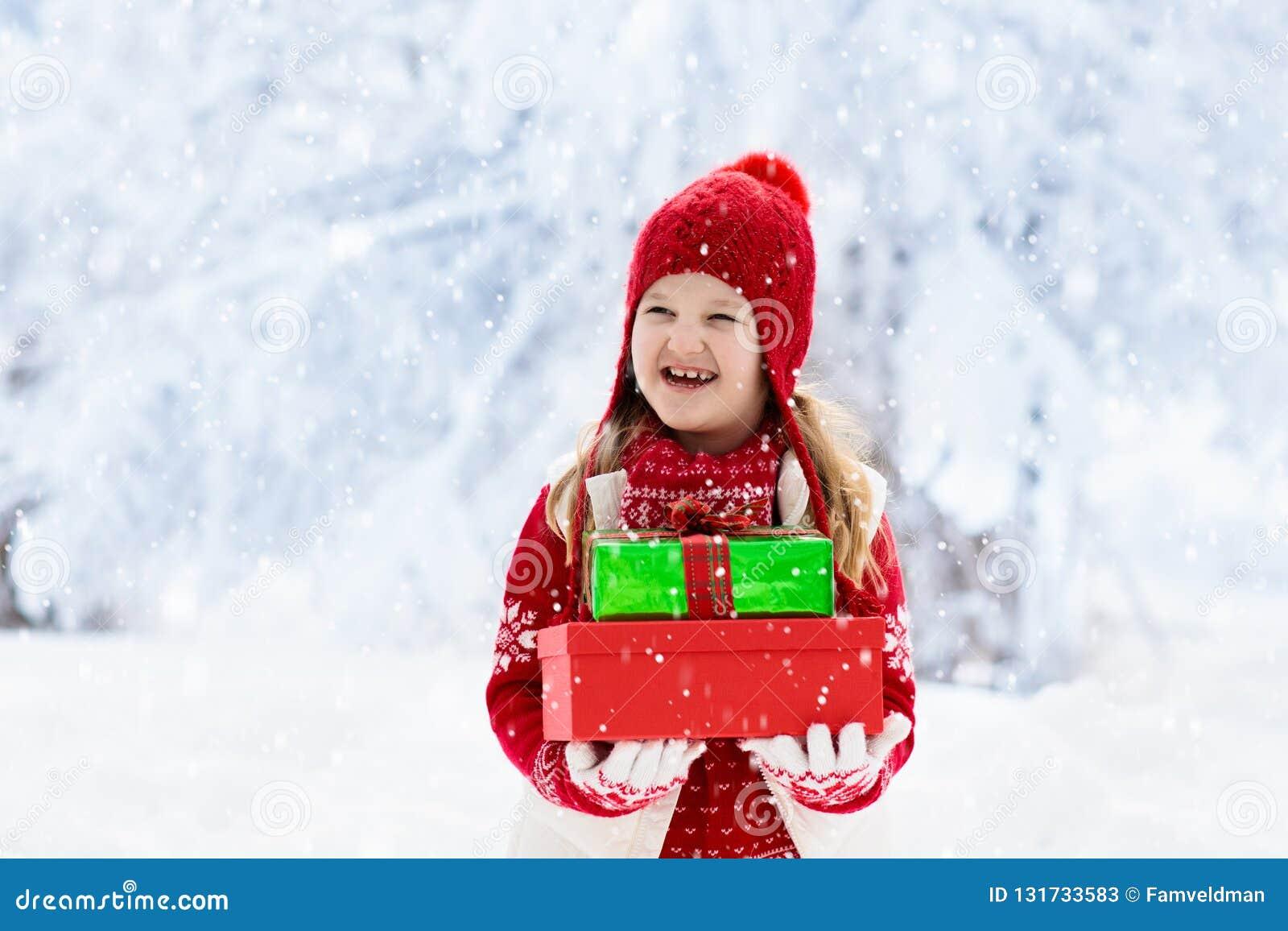 Criança no chapéu vermelho com presentes de Natal e presentes na neve Divertimento exterior do inverno As crianças jogam no parqu