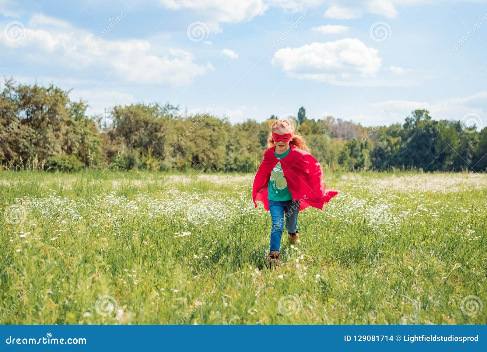 Criança no corredor vermelho do cabo e da máscara do super-herói no prado