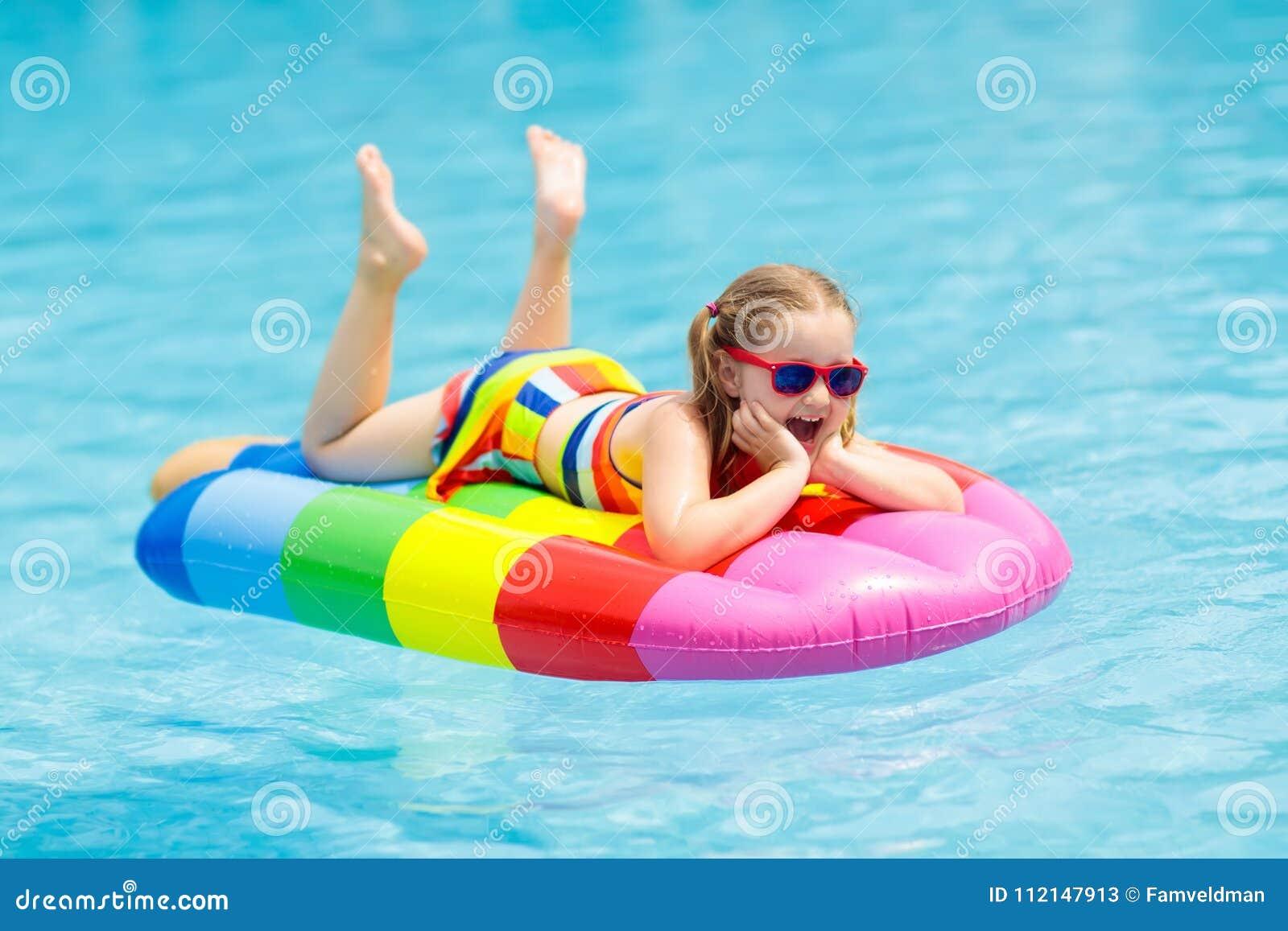 Criança no flutuador inflável na piscina