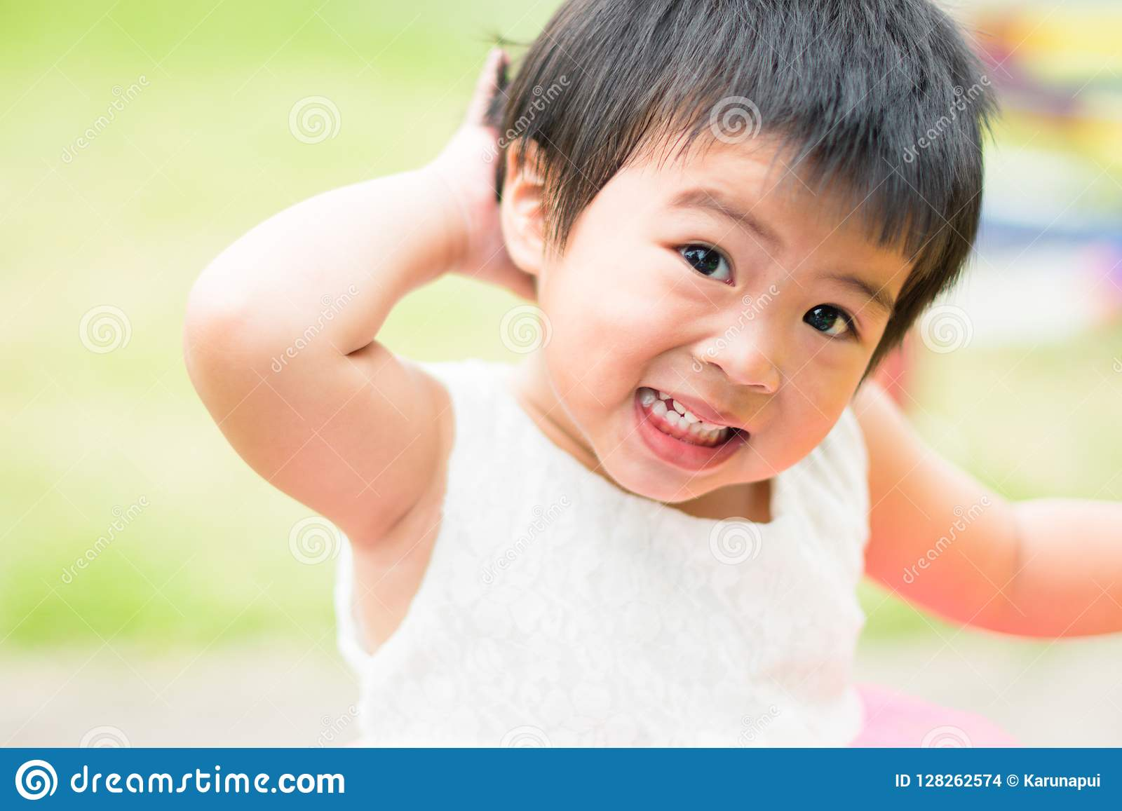 Criança pequena asiática que grita no fundo do campo de jogos