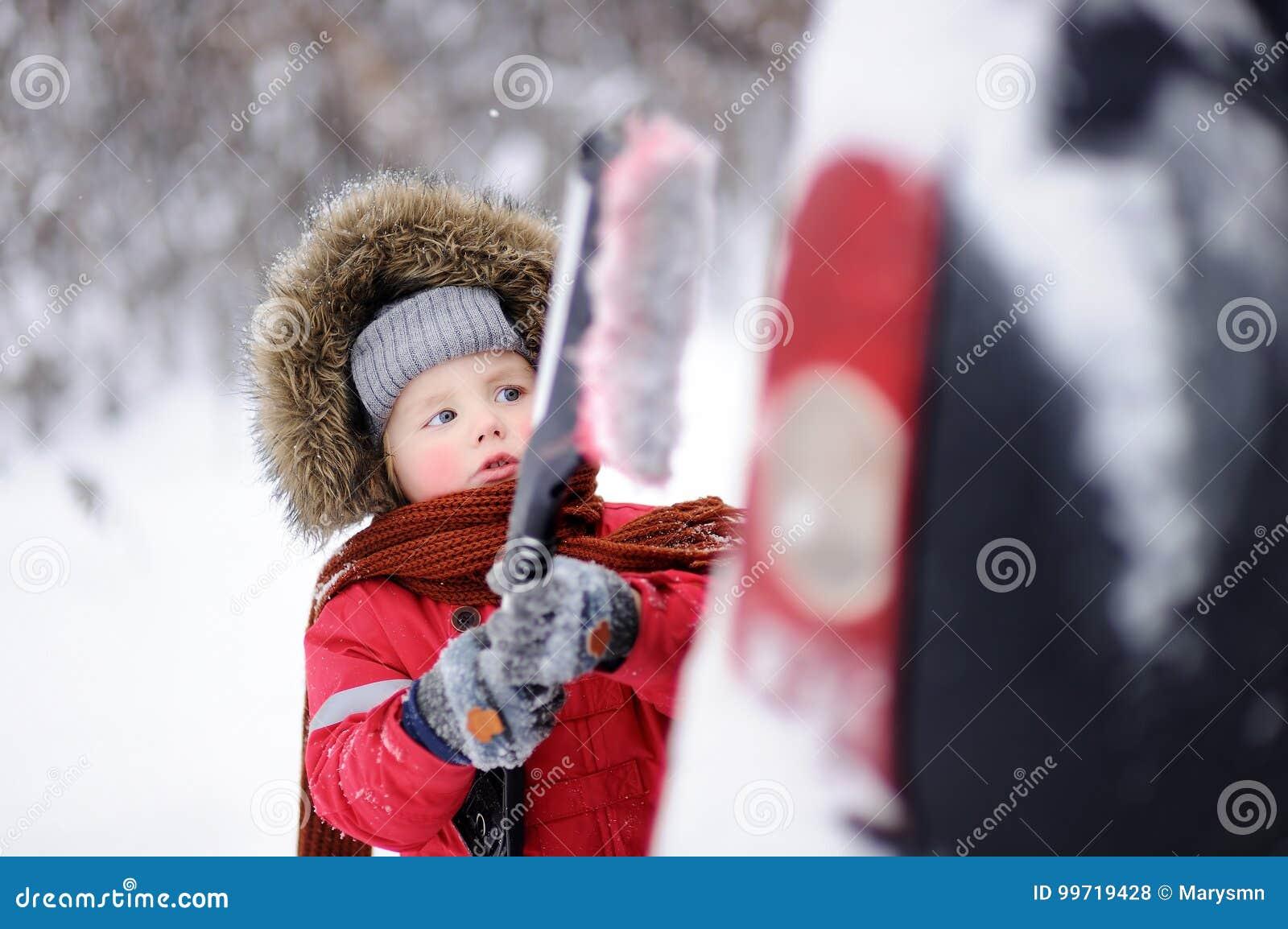 Criança pequena bonito que ajuda a escovar uma neve de um carro