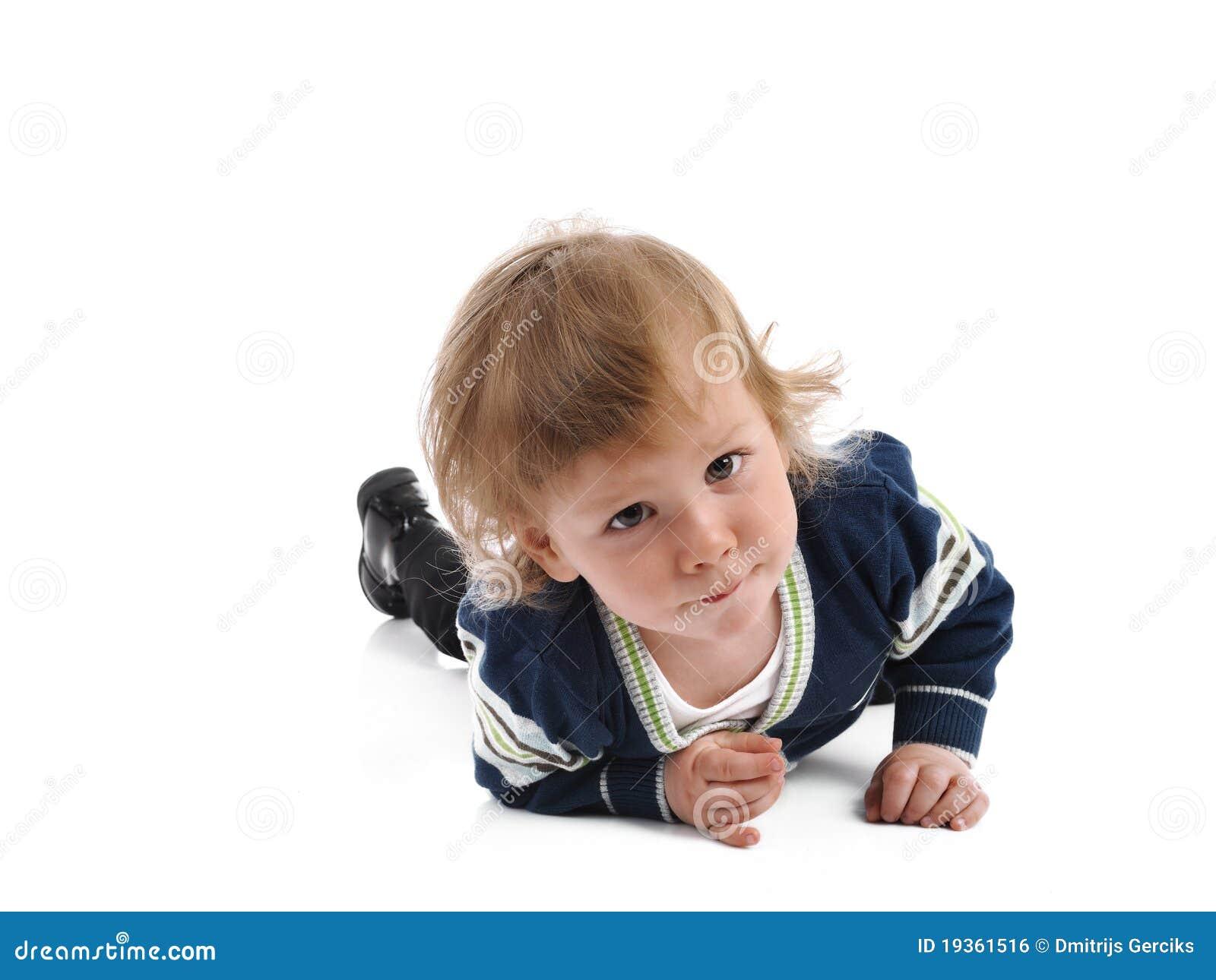 Criança pequena bonito que sorri no assoalho. isolado