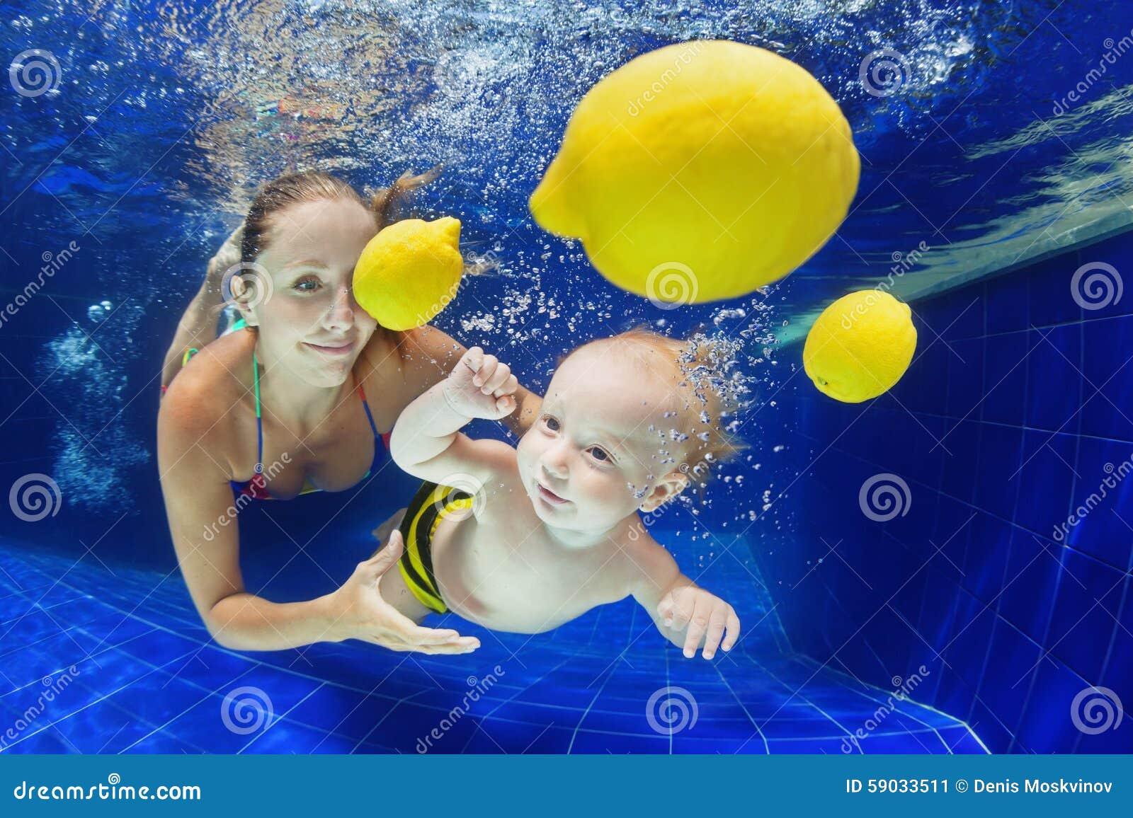 Criança pequena com a mãe que nada debaixo d água na associação