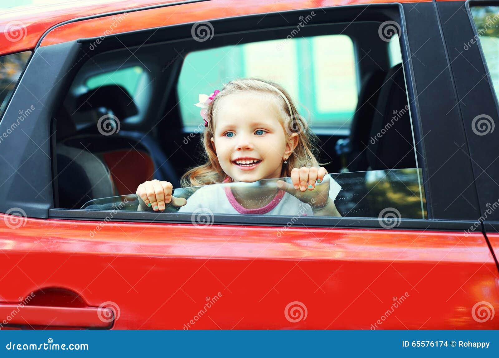 Criança pequena de sorriso do retrato que senta-se no carro vermelho
