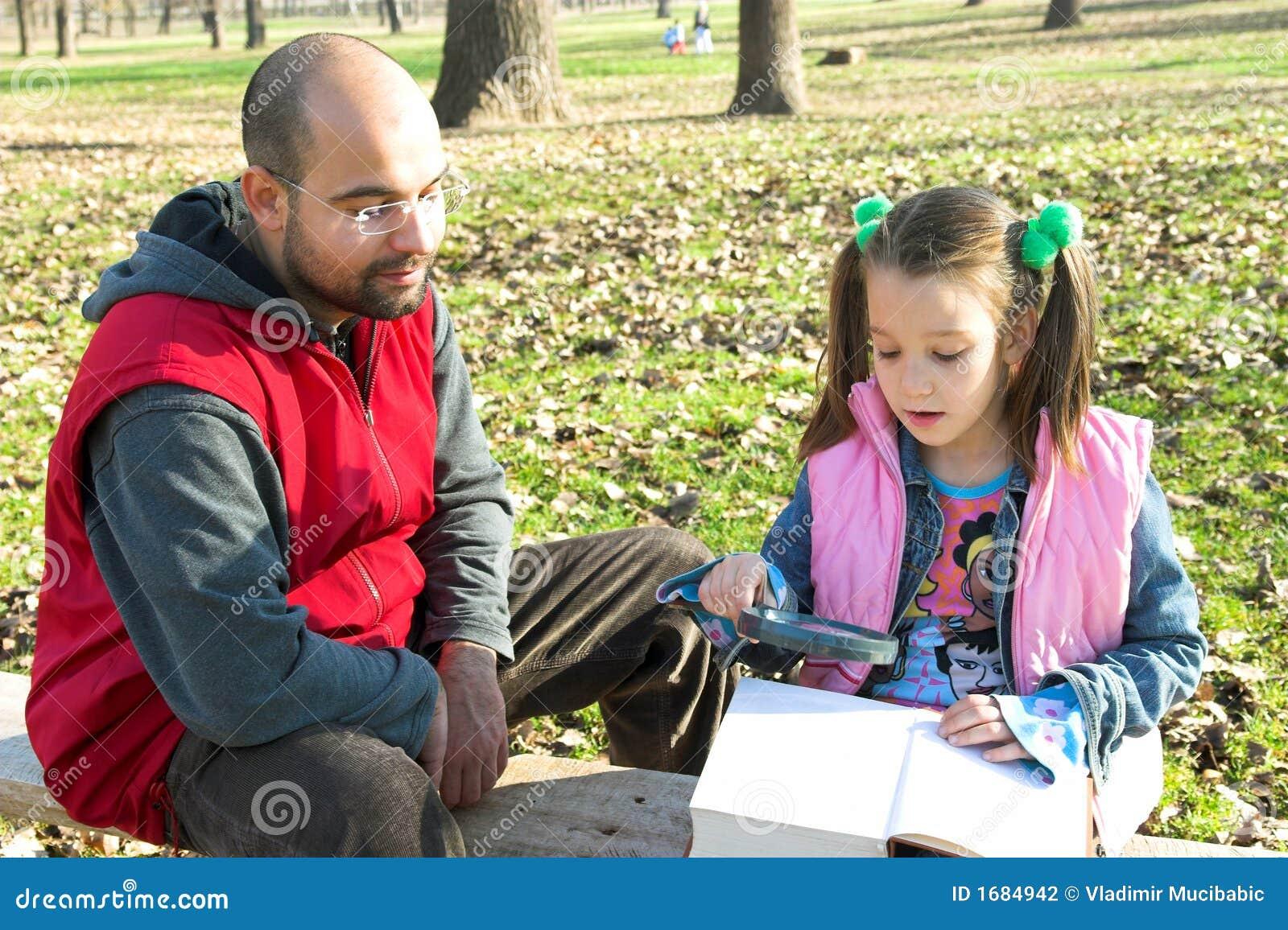 Criança pequena e pai bonitos que lêem o livro